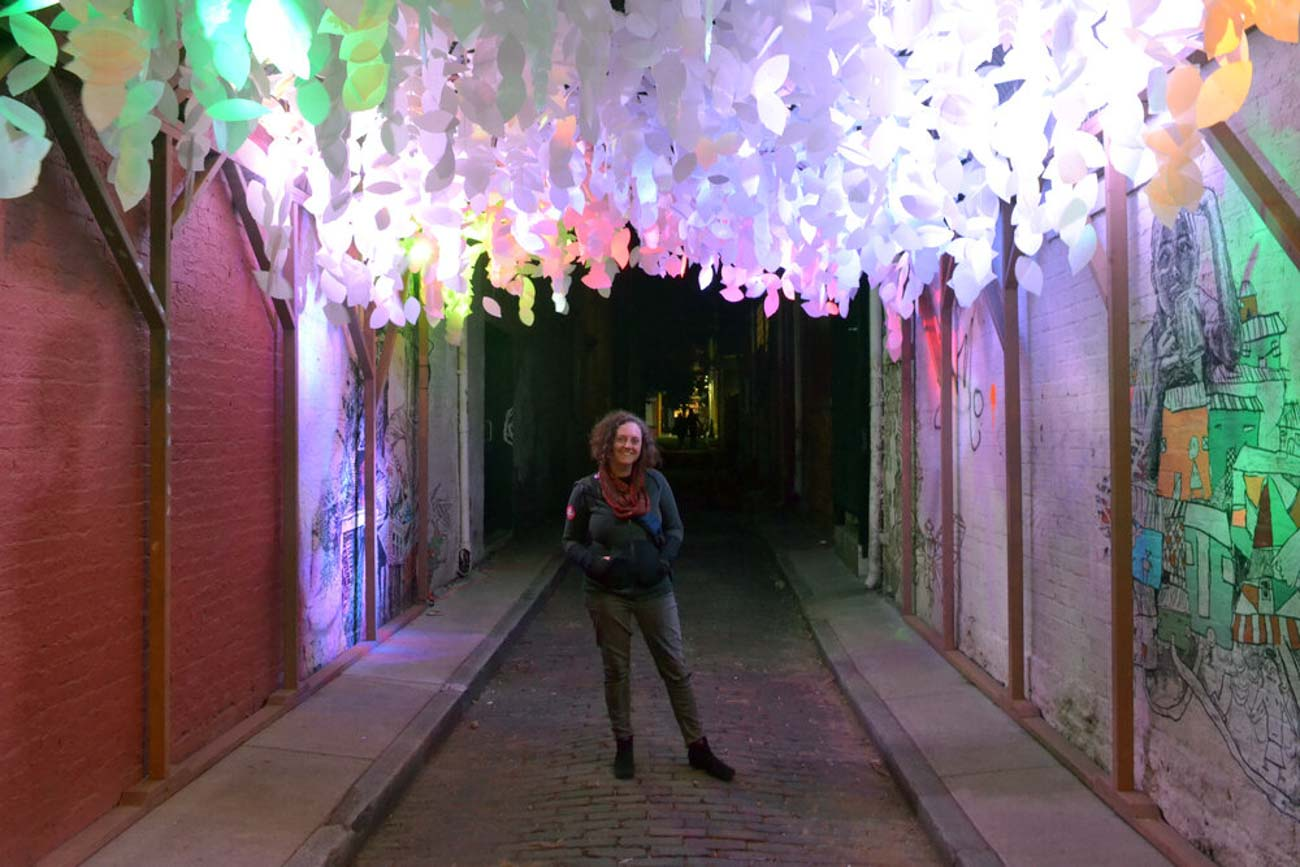 "Pictured: Jessica Wolf / ""Arborealis"" is the name of Jessica's sculpture that she displayed in BLINK. It was located in an alley near Findlay Market and consisted of over 3,000 paper leaves, 12 LED lights, and had a soothing recording of crickets and frogs playing as people walked by it. The leaves were populated with critters like frogs, spiders, geckos, and butterflies. / Image courtesy of Paper Acorn // Published: 6.18.20"