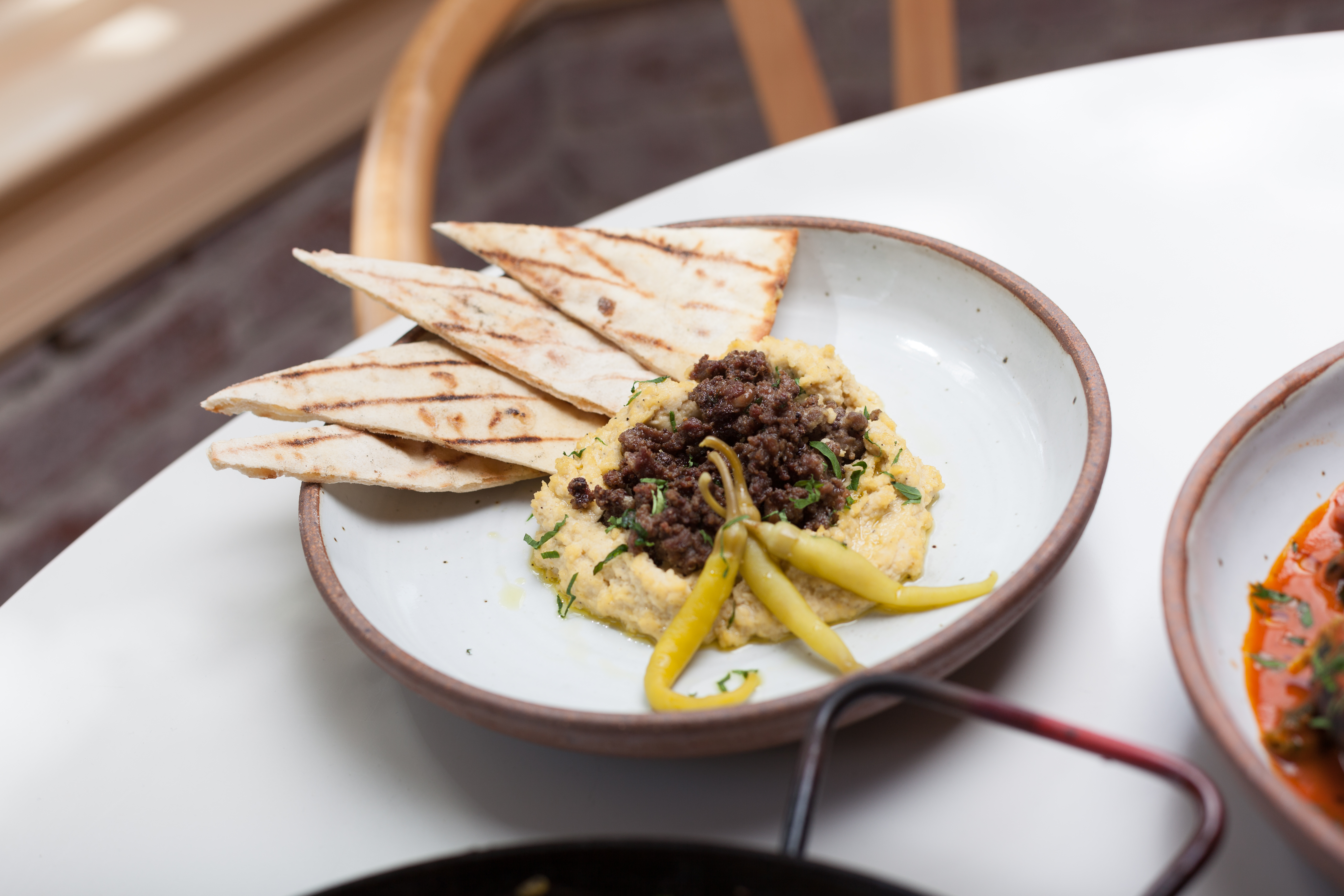 This Moroccan spread made with pureed chickpeas has similar DNA to Middle Eastern hummus. It comes topped off with pickled round lamb fragrant with cumin and cinnamon, and pickled Guindilla peppers. (Image: Bobby Spero)