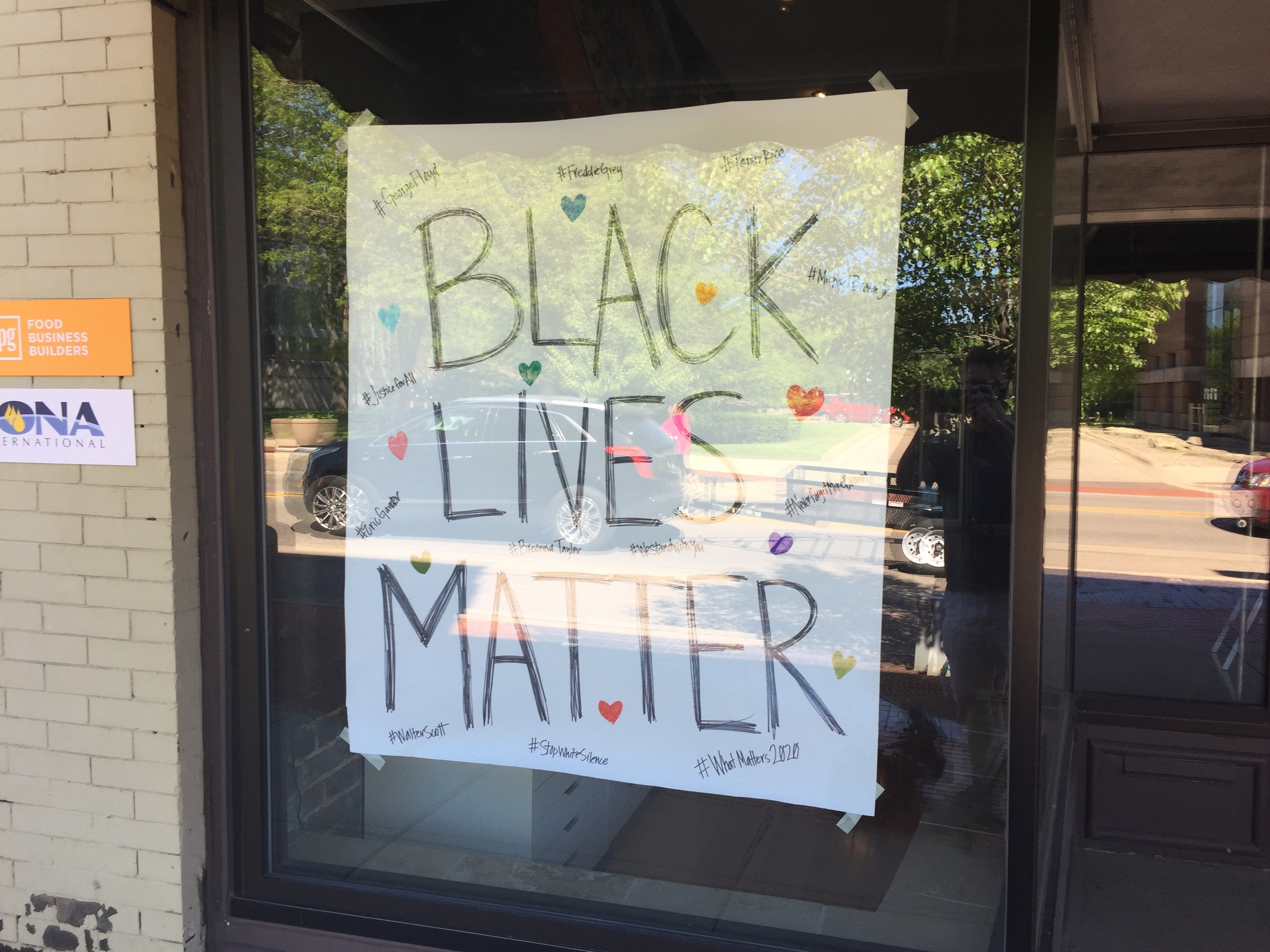 Businesses taped signs to their windows in Battle Creek in protest of the death of George Floyd. (WWMT/Matt Miller)