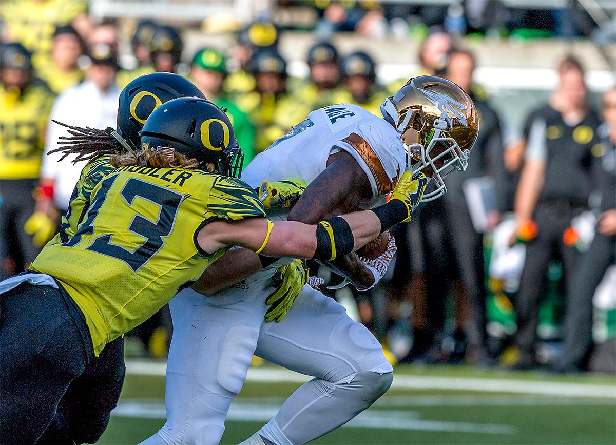 The Sun Devils' Kalen Ballage (#7) tries to push through as the Ducks try to stop his run. The Oregon Ducks broke their losing streak by defeating the ASU Sun Devils on Saturday 54-35. Photo by August Frank, Oregon News Lab