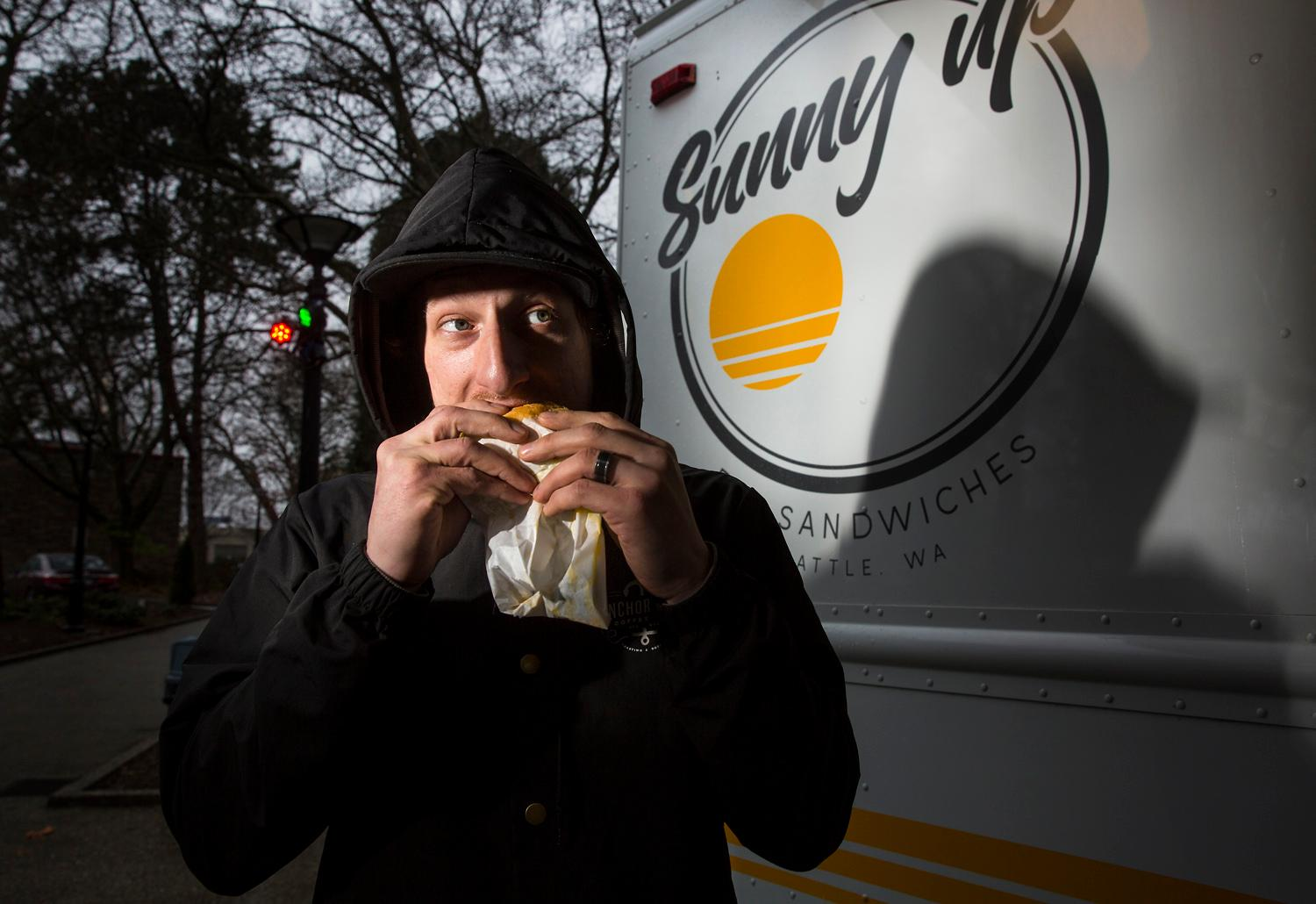 A customer chows down on one of the breakfast sandwiches prepared by the Sunny Up food truck. The truck specializes in serving breakfast sandwiches that are named after the owner's favorite and most influential women. (Sy Bean / Seattle Refined)