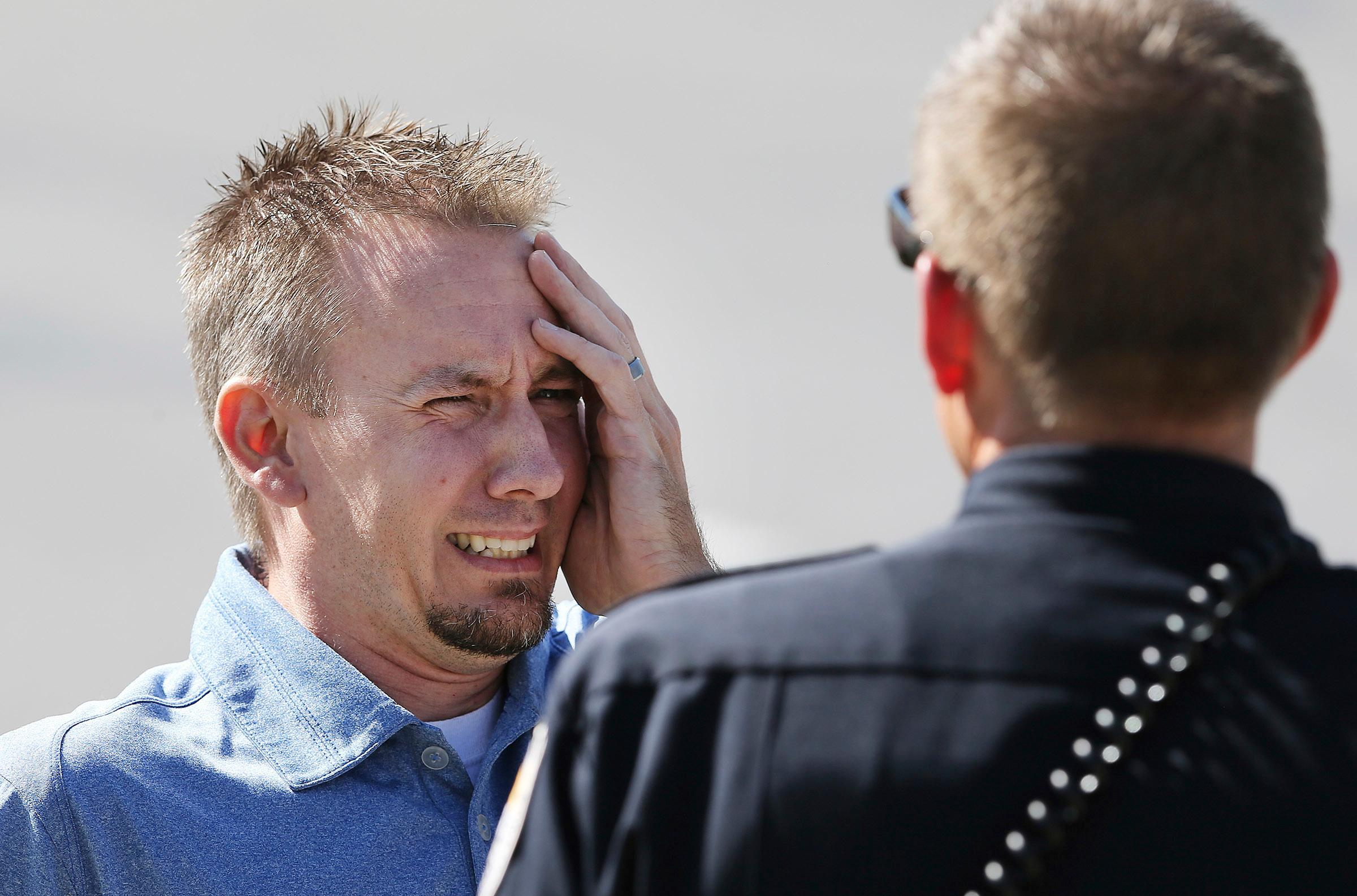 A man reacts as he talks to a Sandy police officer after a fatal shooting in the Salt Lake City suburb that left several people dead with another two injured, Tuesday, June 6, 2017, in Sandy, Utah. The shooting in a middle-class neighborhood in Sandy was reported to police as a domestic dispute, said Police Sgt. Jason Nielsen. (Scott G Winterton/The Deseret News via AP)
