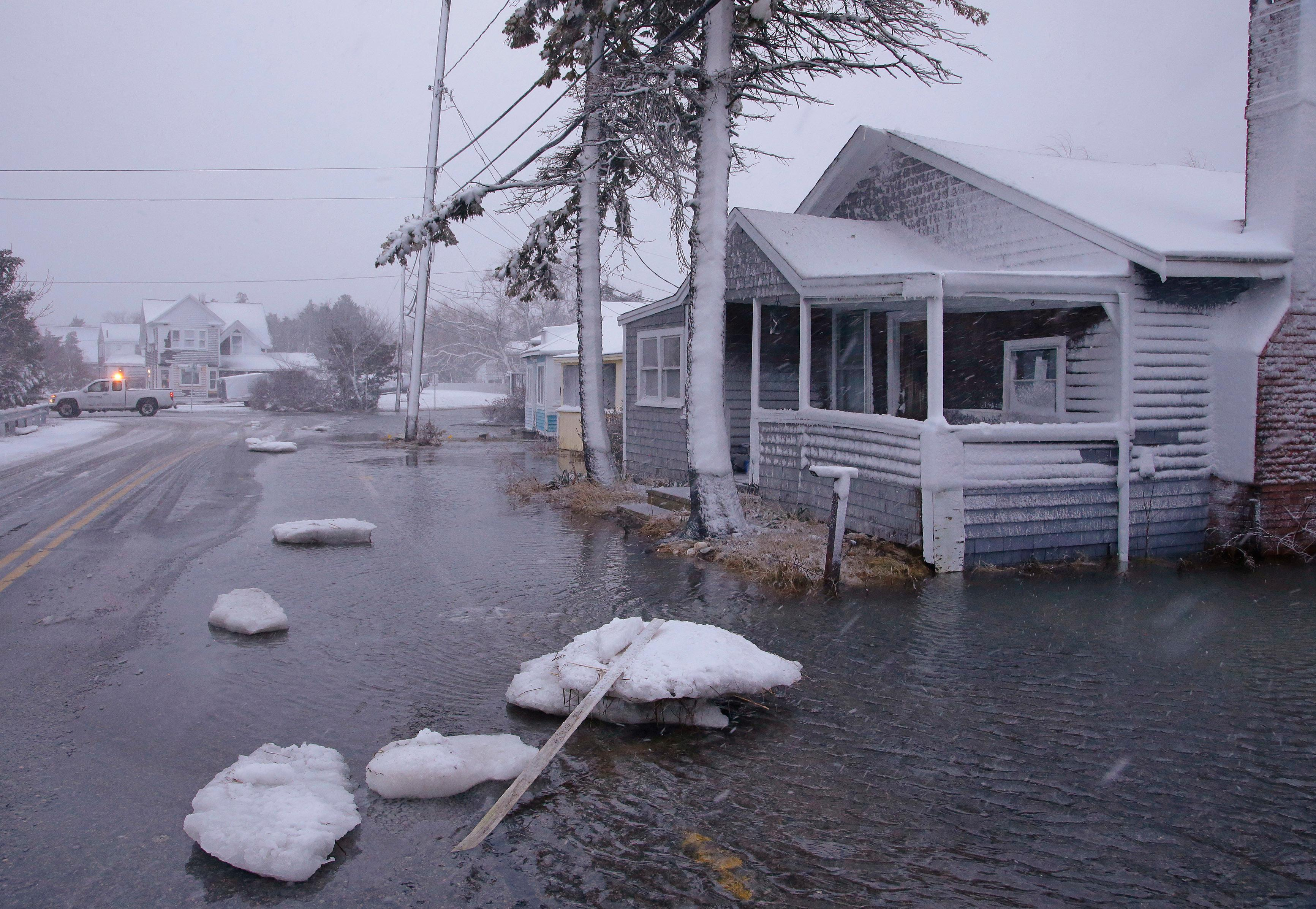 Large chunks of sea ice strewn Ferry Street in front of a flooded house as a utilities truck passes through a nearby intersection Thursday, Jan. 4, 2018, in Marshfield, Mass. The National Weather Service has issued a blizzard warning for Thursday that extends from eastern Long Island north to coastal New Hampshire and Maine. Most of the rest of southern New England is under a winter storm watch. (AP Photo/Stephan Savoia)
