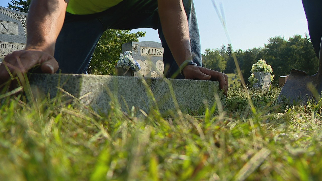 Footstones left standing along a guardrail at Green Hills Cemetery in Leicester were finally placed Tuesday, thanks to volunteers from L&S Landscape. (Photo credit: WLOS staff)
