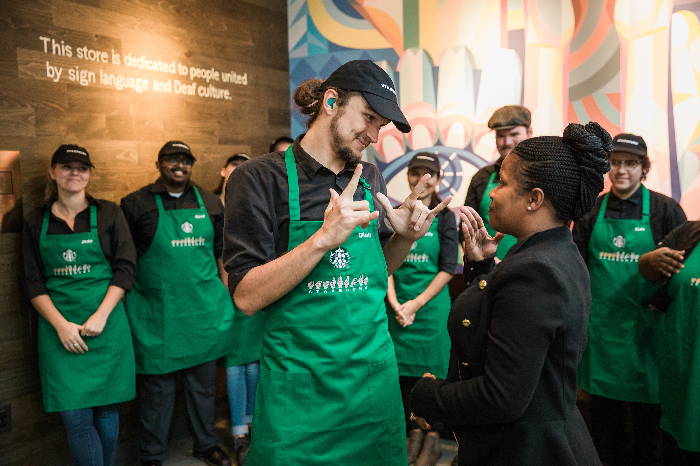 Starbucks District Manager Margaret Houston presents an apron to partner Glen Cole on Saturday, October 20, 2018 at Starbucks first U.S. Signing Store in Washington D.C.{ }(Image: Joshua Trujillo, Starbucks)