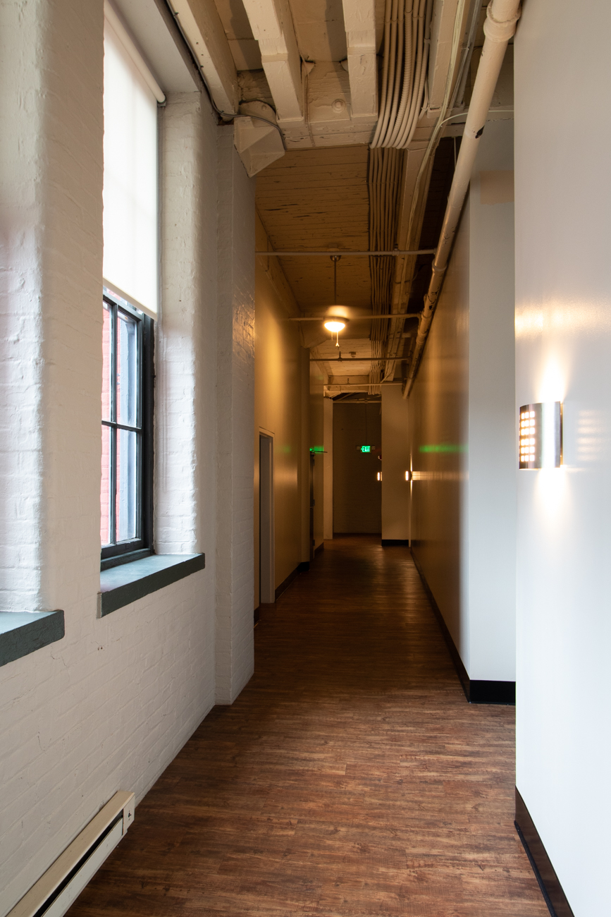 A hallway with Sycamore Place highlights historic character merged with modern charm.{ }/ Image: Ronny Salerno // Published: 2.6.19