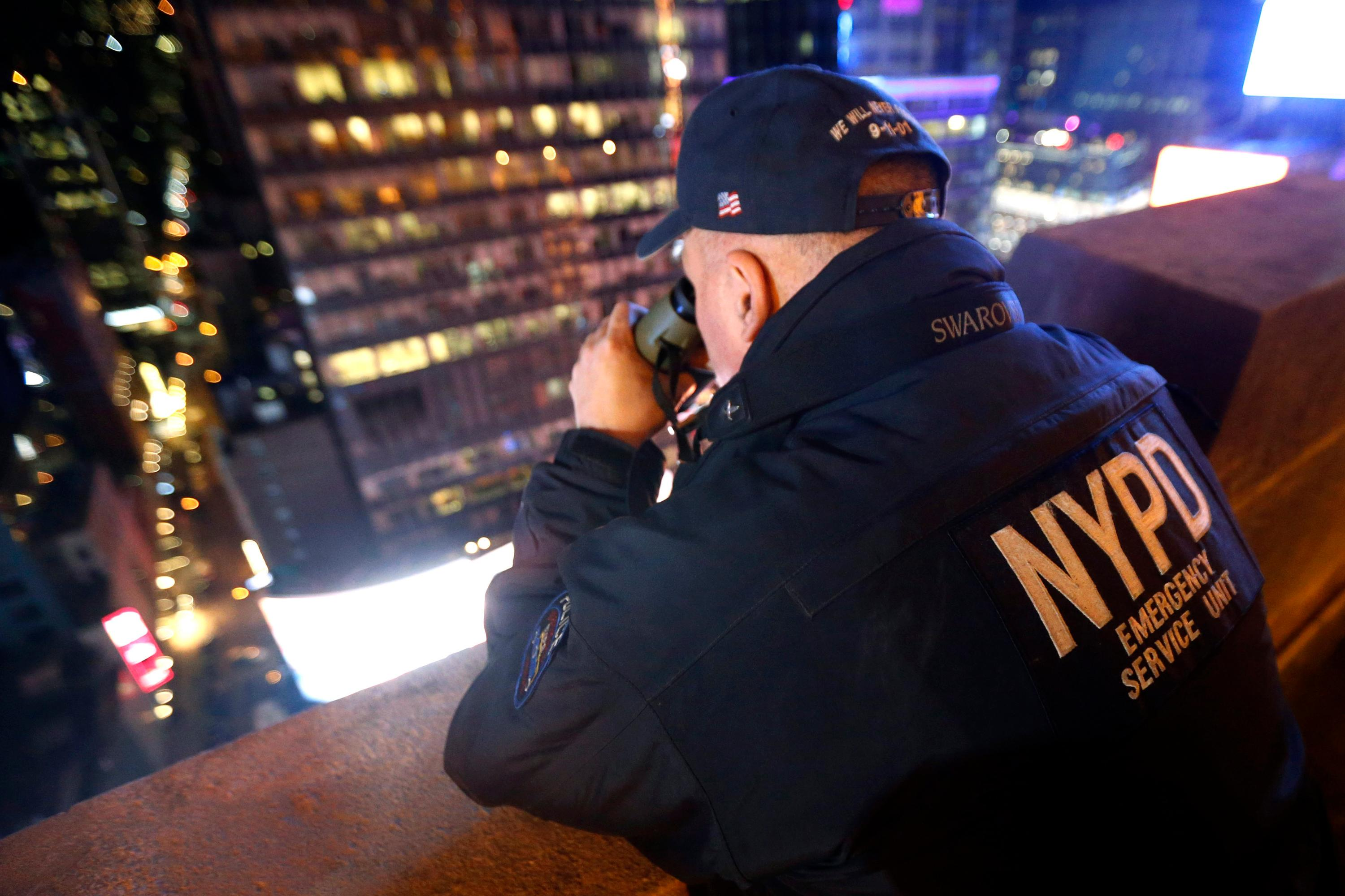 FILE - In this Dec. 31, 2015 file photo, a New York police officer uses binoculars while keeping watch from a rooftop along Times Square during New Year's Eve celebrations in New York. A Las Vegas shooting from a high-rise hotel that killed dozens of people in a packed concert below on Sunday, Oct. 1, 2017, has forced other cities to examine their tactics for dealing with this kind of nightmare scenario. In New York, which hosts Times Square New Year's Eve and other events surrounded by high-rises, police say they use rooftop snipers to scan for threats, and make security sweeps of nearby hotels. (AP Photo/Julio Cortez, File)