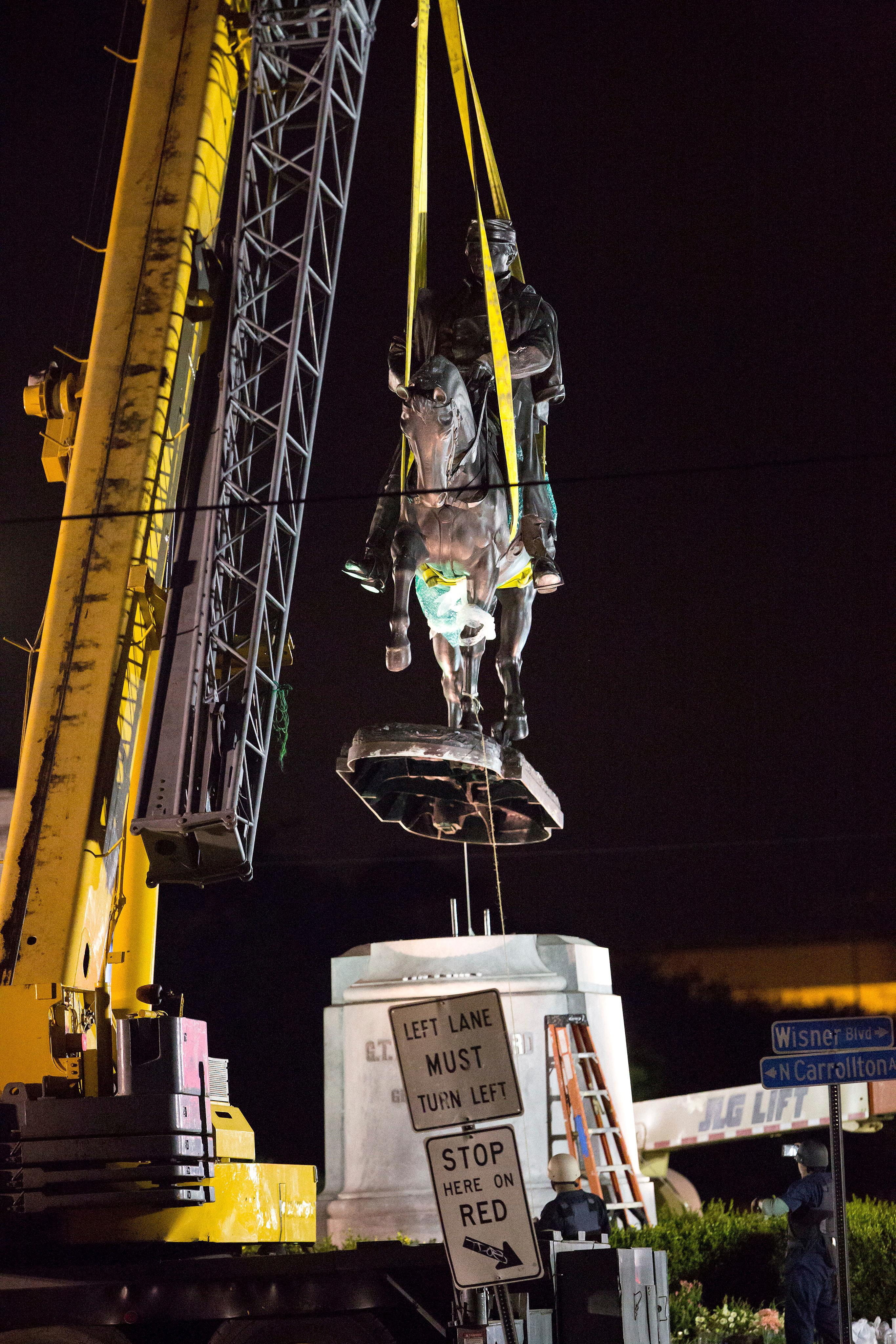 A statue of Confederate general P.G.T. Beauregard is removed just after 3 a.m. Central Standard Time Wednesday, May 17, 2017, from the entrance to City Park in New Orleans.   The removal of the statue comes after the city has already taken down a statue of Jefferson Davis, the Confederacy's only president,  and a memorial to a white rebellion against a biracial Reconstruction-era government in the city.  (AP Photo/Scott Threlkeld)