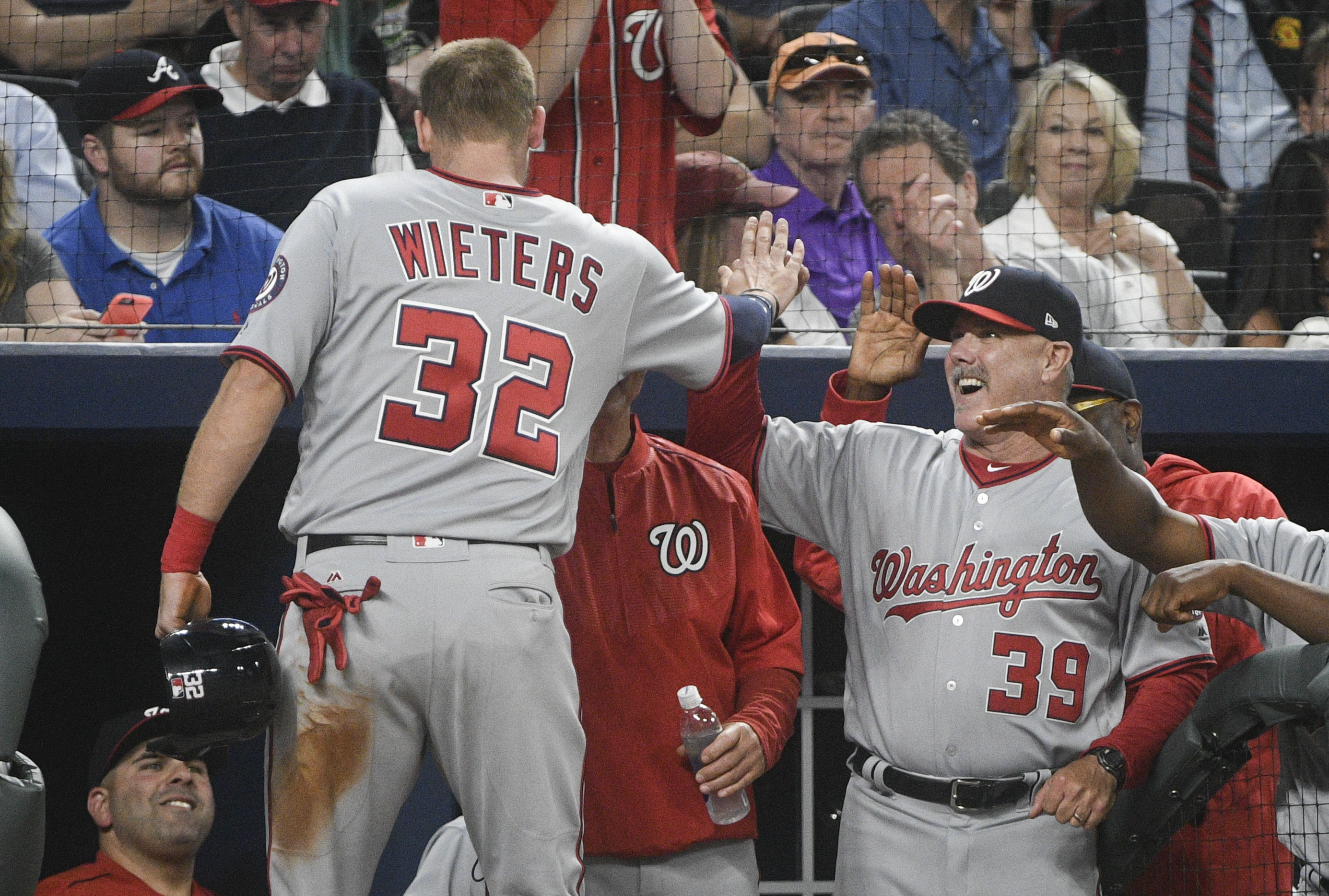 Washington Nationals catcher Matt Wieters (32) is congratulated in the dugout by hitting coach Rick Schu (39) after scoring during the fifth inning of a baseball game agains the Atlanta Braves, Tuesday, April 18, 2017, in Atlanta. (AP Photo/John Amis)