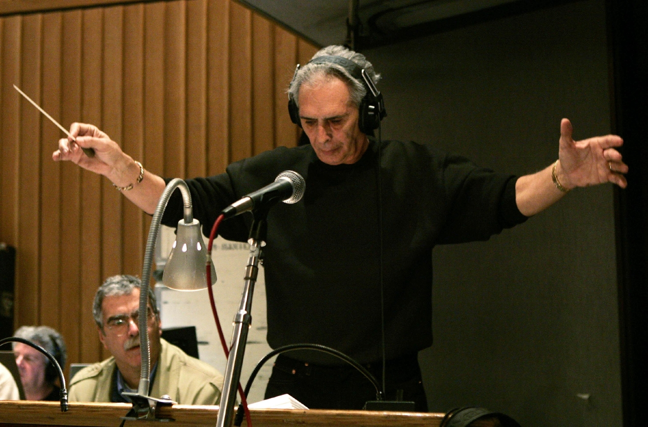 "FILE – In this Feb. 21, 2005, file photo, composer and conductor Bill Conti, music director of the 77th Academy Awards, conducts the show's orchestra during a rehearsal at Capitol Recording Studios in Los Angeles. Four decades after the Nov. 21, 1976, premiere of ""Rocky,"" the movie's reach is international, and the title character's underdog tale of determination, grit and sleepy-eyed charm still resonates with fans. (AP Photo/Kevork Djansezian, File)"