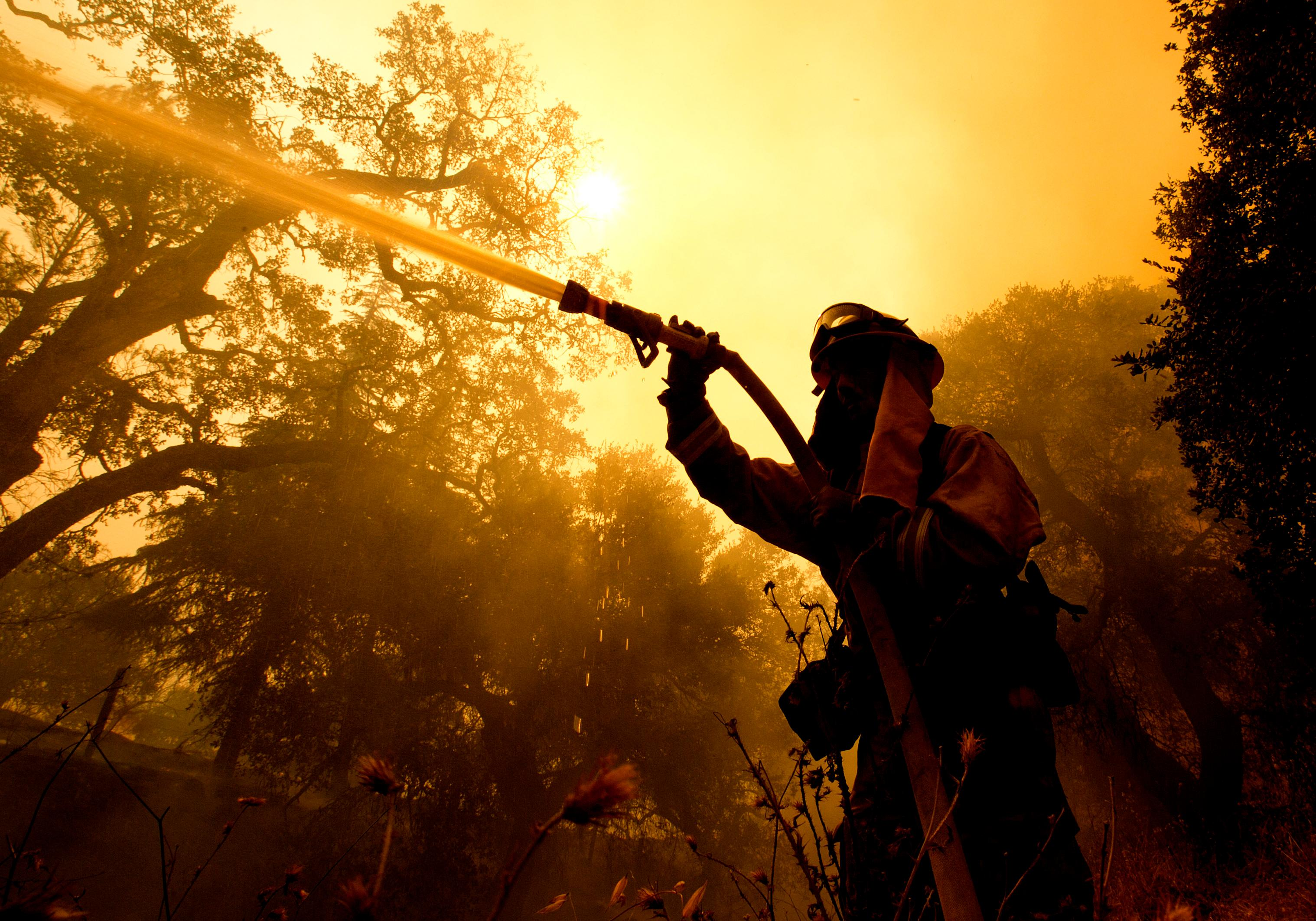 Napa County firefighter Jason Sheumann sprays water on a home as he battles flames from a wildfire Monday, Oct. 9, 2017, in Napa, Calif. Wildfires whipped by powerful winds swept through Northern California sending residents on a headlong flight to safety through smoke and flames as homes burned. (AP Photo/Rich Pedroncelli)