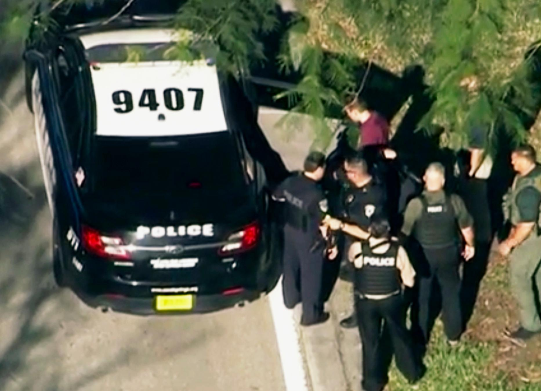 In this frame grab from video provided by WPLG-TV, law enforcement personnel arrest an unidentified man (in dark red), following a shooting at Marjory Stoneman Douglas High School in Parkland, Fla., Wednesday, Feb. 14, 2018. (WPLG-TV via AP)<p></p>