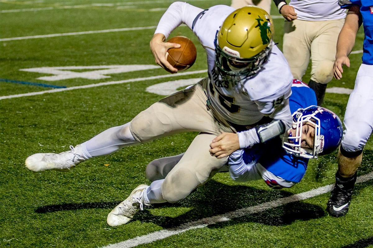 The Lancers' Cole Jensen (#22) pulls the Buckaroos' Nick Bower (#15) to the ground. The Churchill Lancers defeated the Pendleton Buckaroos 42-15, in the first round of the state 5A playoffs. Photo by August Frank, Oregon News Lab