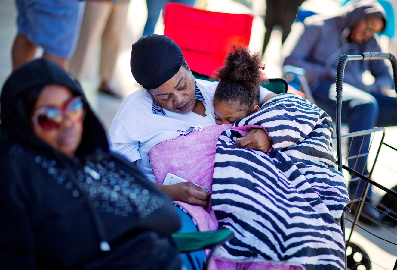 Jackie Archer, from left, Kathy Wilcox and her granddaughter Aaliyah Wilcox-Chid, 6, sleep while waiting in line for the box office to open for tickets for Muhammad Ali's Jenazah service at Freedom Hall Tuesday, June 7, 2016, in Louisville, Ky. The day before his star-studded funeral, members of Ali's Islamic faith will get their chance to say a traditional goodbye during a Jenazah, a traditional Muslim funeral. (AP Photo/David Goldman)