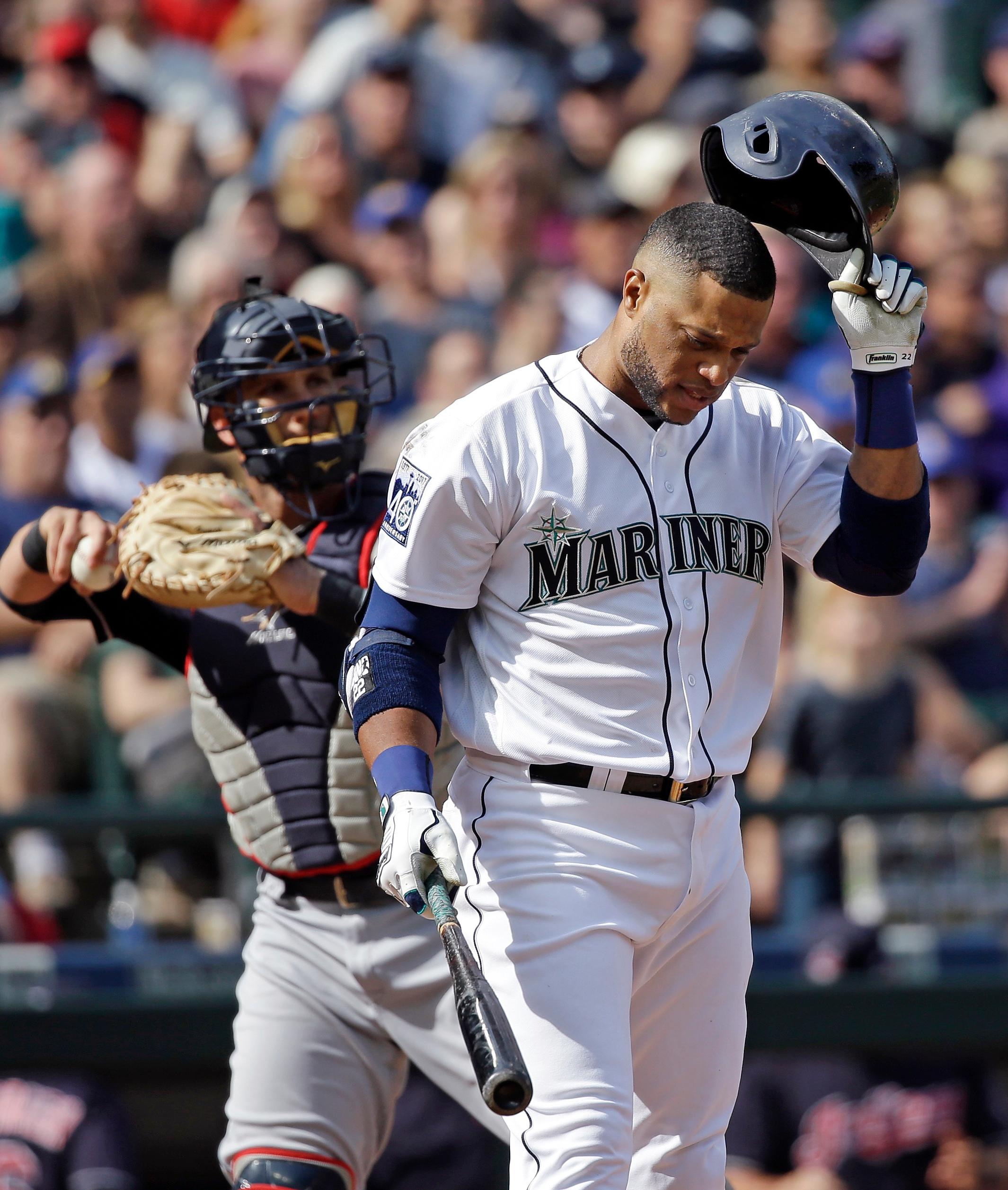FILE- In this Sept. 23, 2017, file photo, Seattle Mariners' Robinson Cano, right, pulls off his batting helmet after striking out to end the third inning of a baseball game as Cleveland Indians catcher Yan Gomes tosses the ball back to the mound in Seattle. Cano has been suspended 80 games for violating baseball's joint drug agreement, the league announced Tuesday, May 15, 2018. (AP Photo/Elaine Thompson, File)