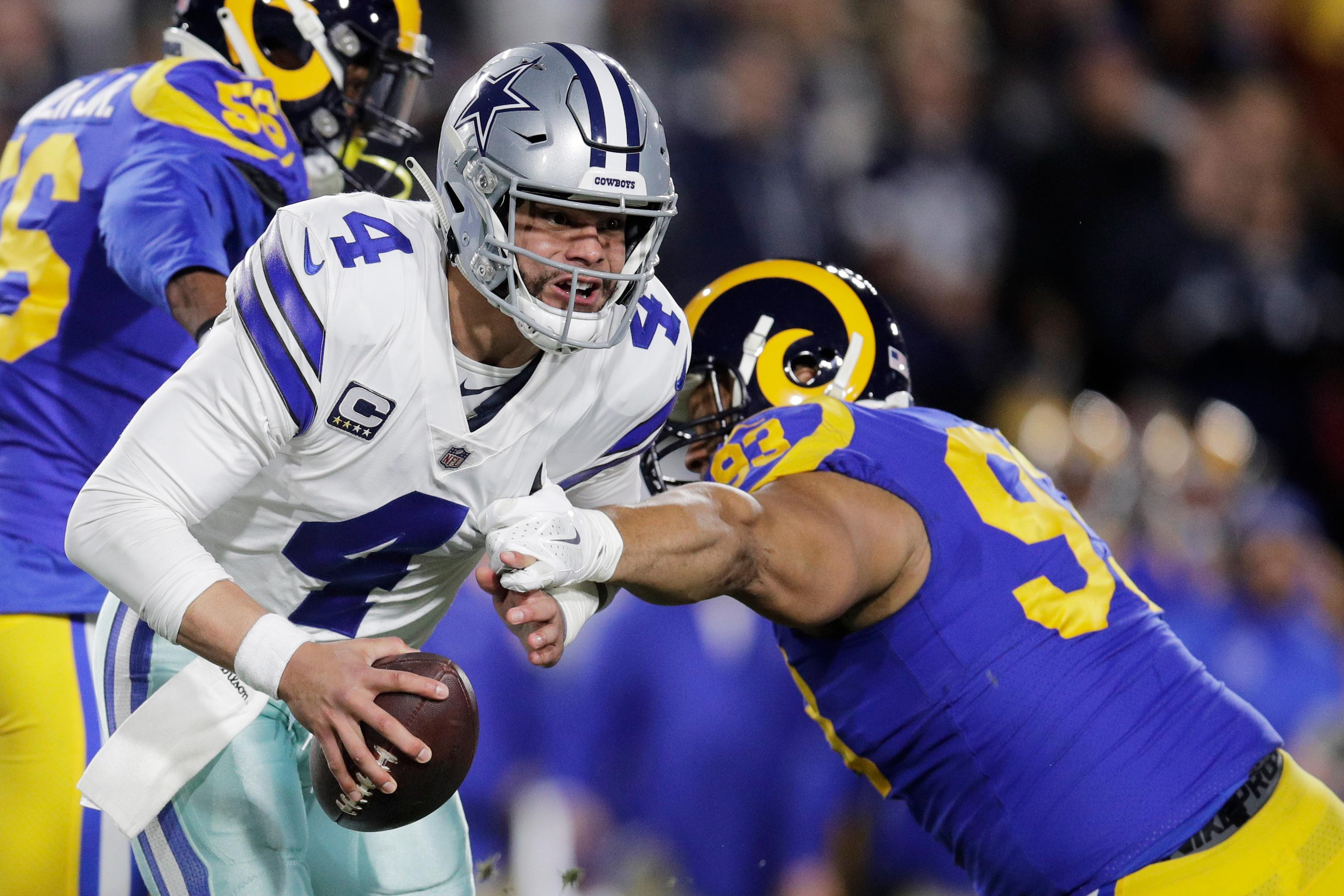 Dallas Cowboys quarterback Dak Prescott breaks away from Los Angeles Rams nose tackle Ndamukong Suh during the first half in an NFL divisional football playoff game Saturday, Jan. 12, 2019, in Los Angeles. (AP Photo/Jae C. Hong)