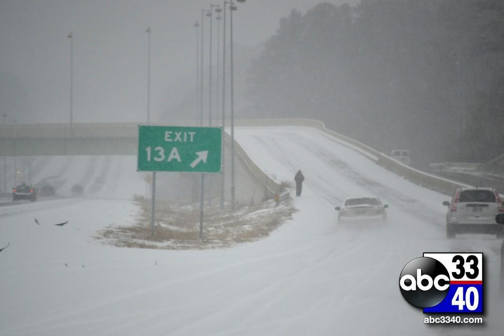 A stranded motorist walks on the Riverchase Galleria flyover off Interstate 459 West in Hoover, Ala. during a winter storm, Tuesday, January 28, 2014.