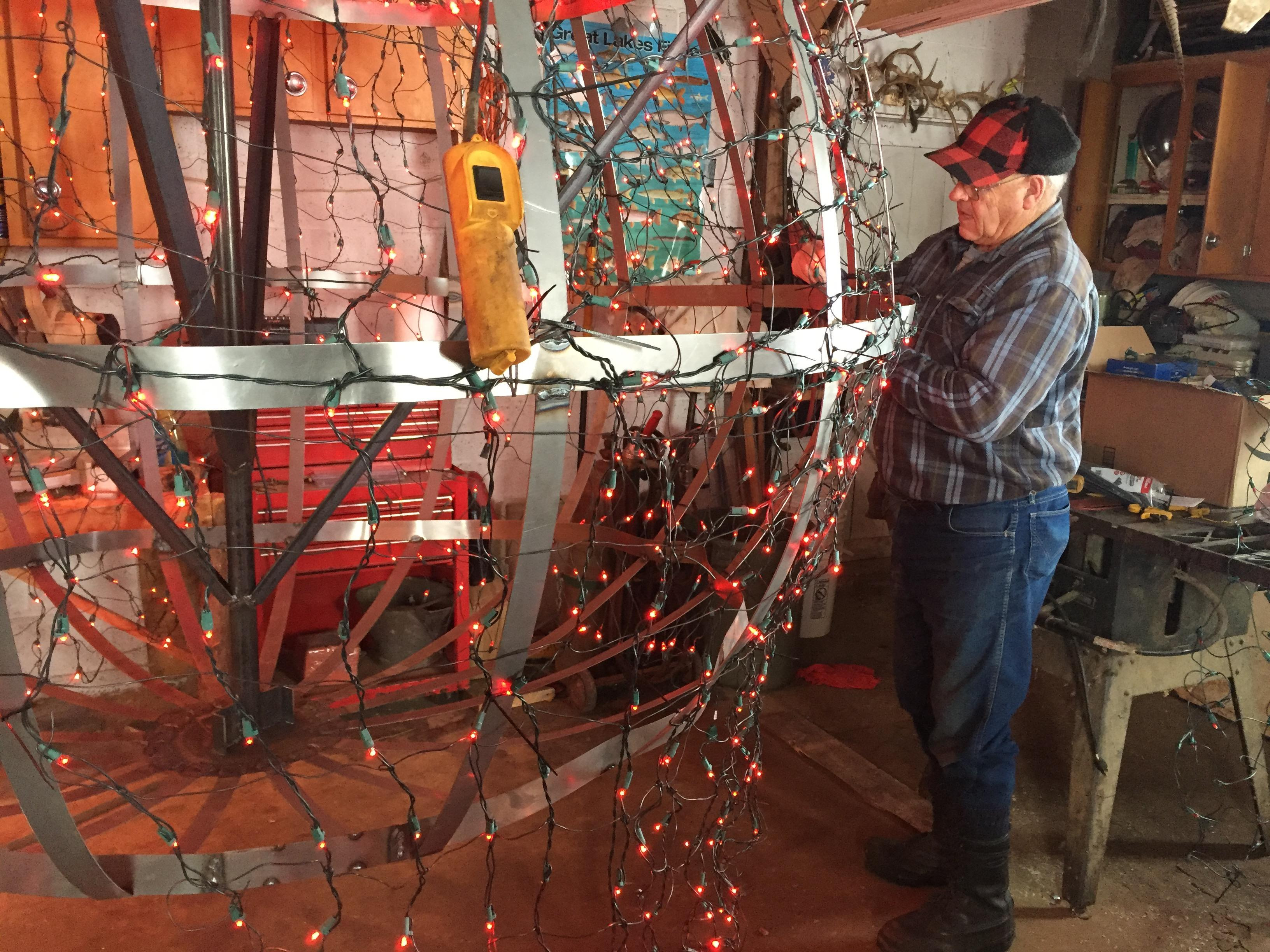 "Duane ""Corky"" Corbisier works on a giant cherry to be used in the Sister Bay New Year's Eve celebration, December 28, 2017 (WLUK/Eric Peterson)"