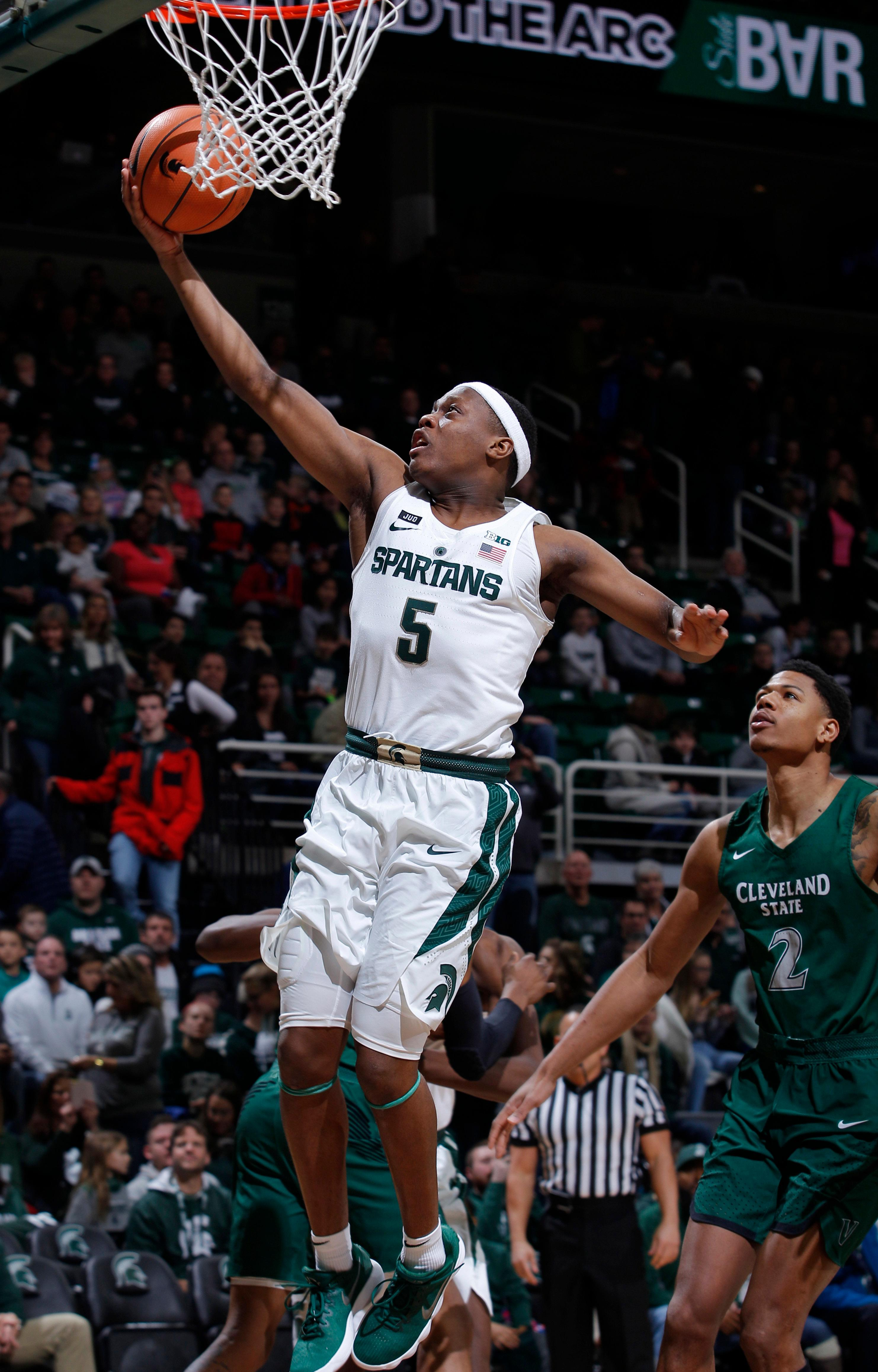 Michigan State's Cassius Winston (5) shoots a layup in front of Cleveland State's Anthony Wright (2) during the first half of an NCAA college basketball game Friday, Dec. 29, 2017, in East Lansing, Mich. (AP Photo/Al Goldis)