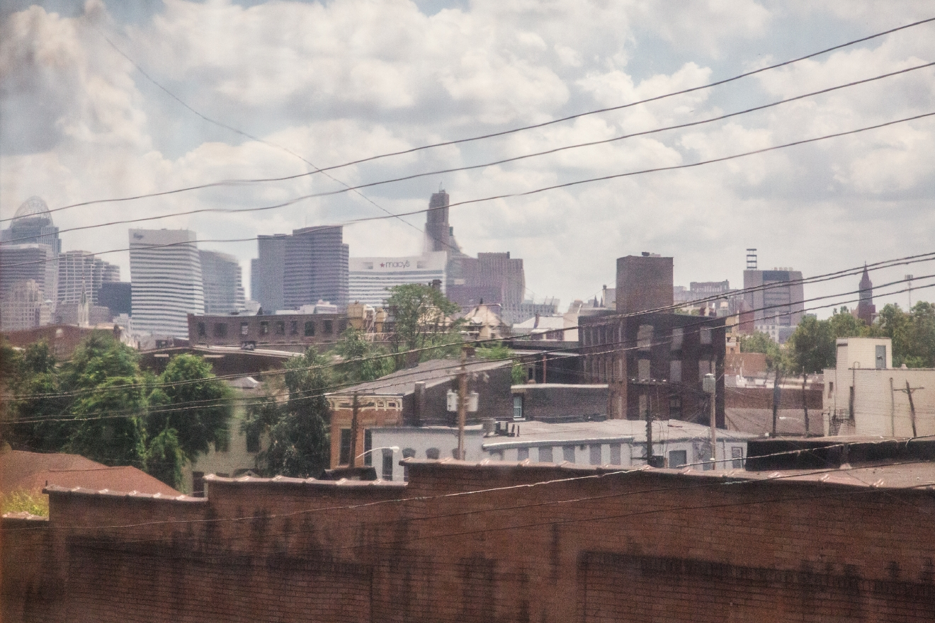 A distorted view of the Cincinnati skyline through old glass windows. / Image: Catherine Viox