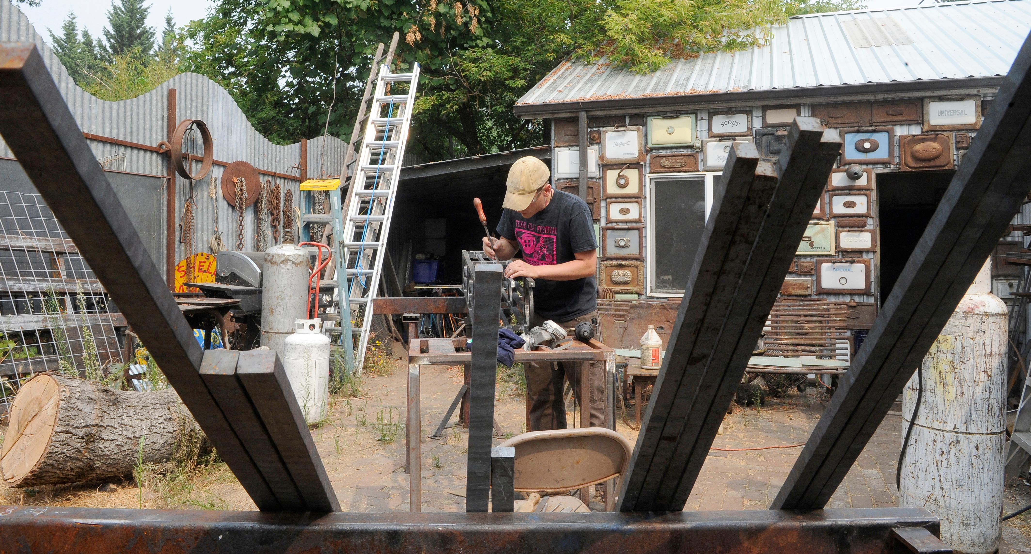 Andy Atkinson / Mail Tribune<br>Colin Ray works on creating an entry gate for a local resident in the back of Ashland Forge.