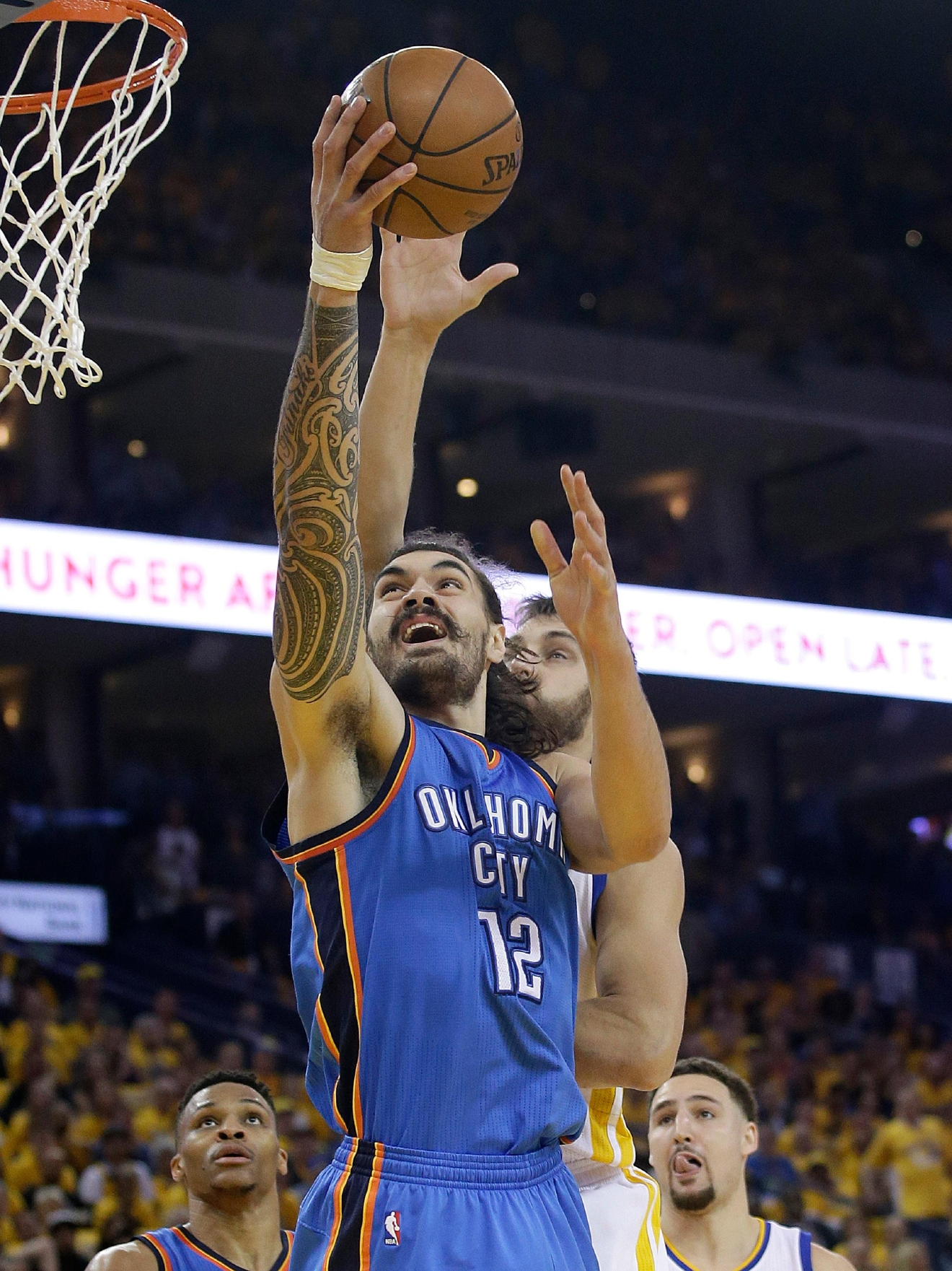 Oklahoma City Thunder center Steven Adams (12) shoots in front of Golden State Warriors center Andrew Bogut during the first half of Game 5 of the NBA basketball Western Conference finals in Oakland, Calif., Thursday, May 26, 2016. (AP Photo/Marcio Jose Sanchez)