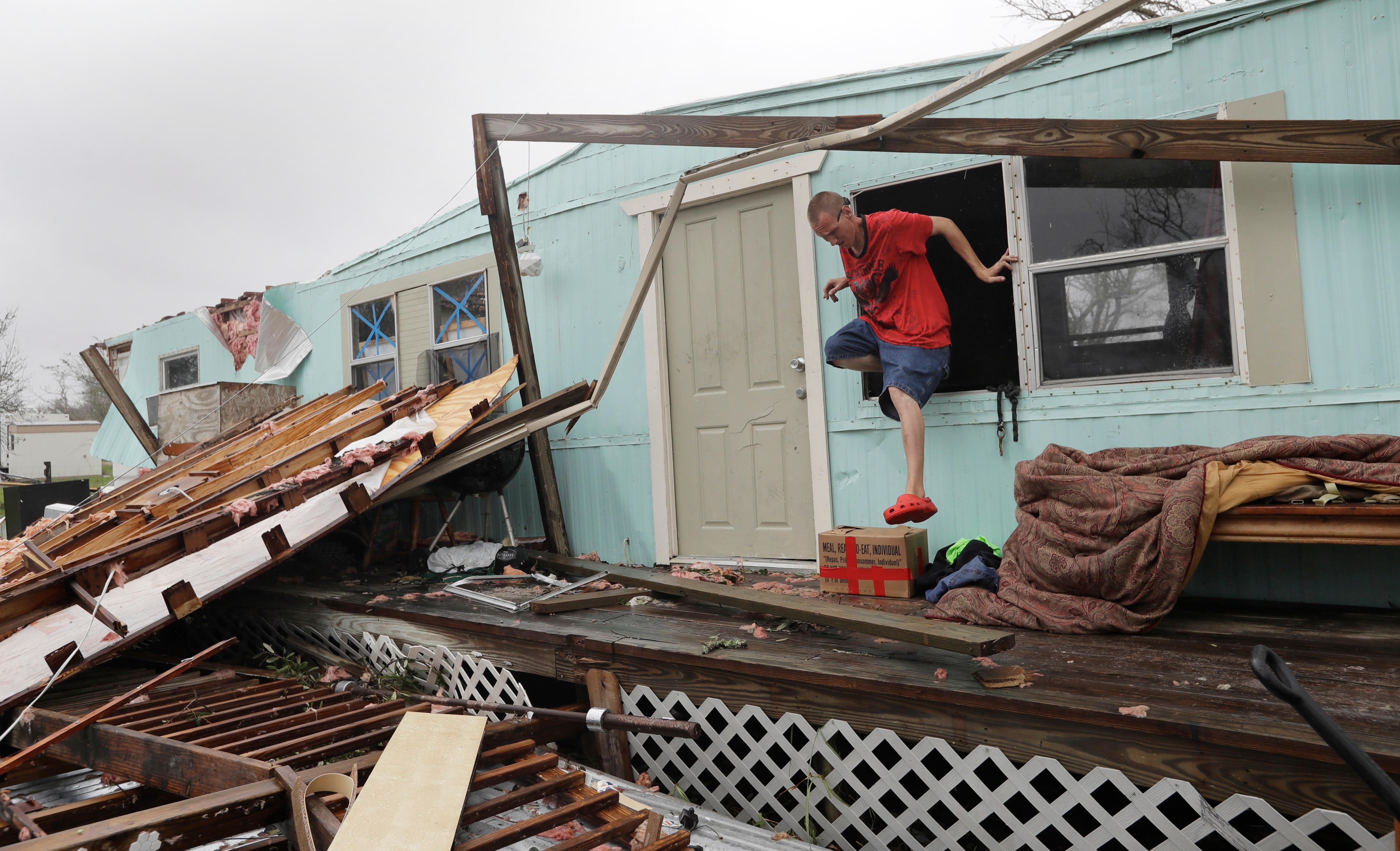 Sam Speights exits a window of his home that was destroyed in the wake of Hurricane Harvey, Monday, Aug. 28, 2017, in Rockport, Texas. (AP Photo/Eric Gay)