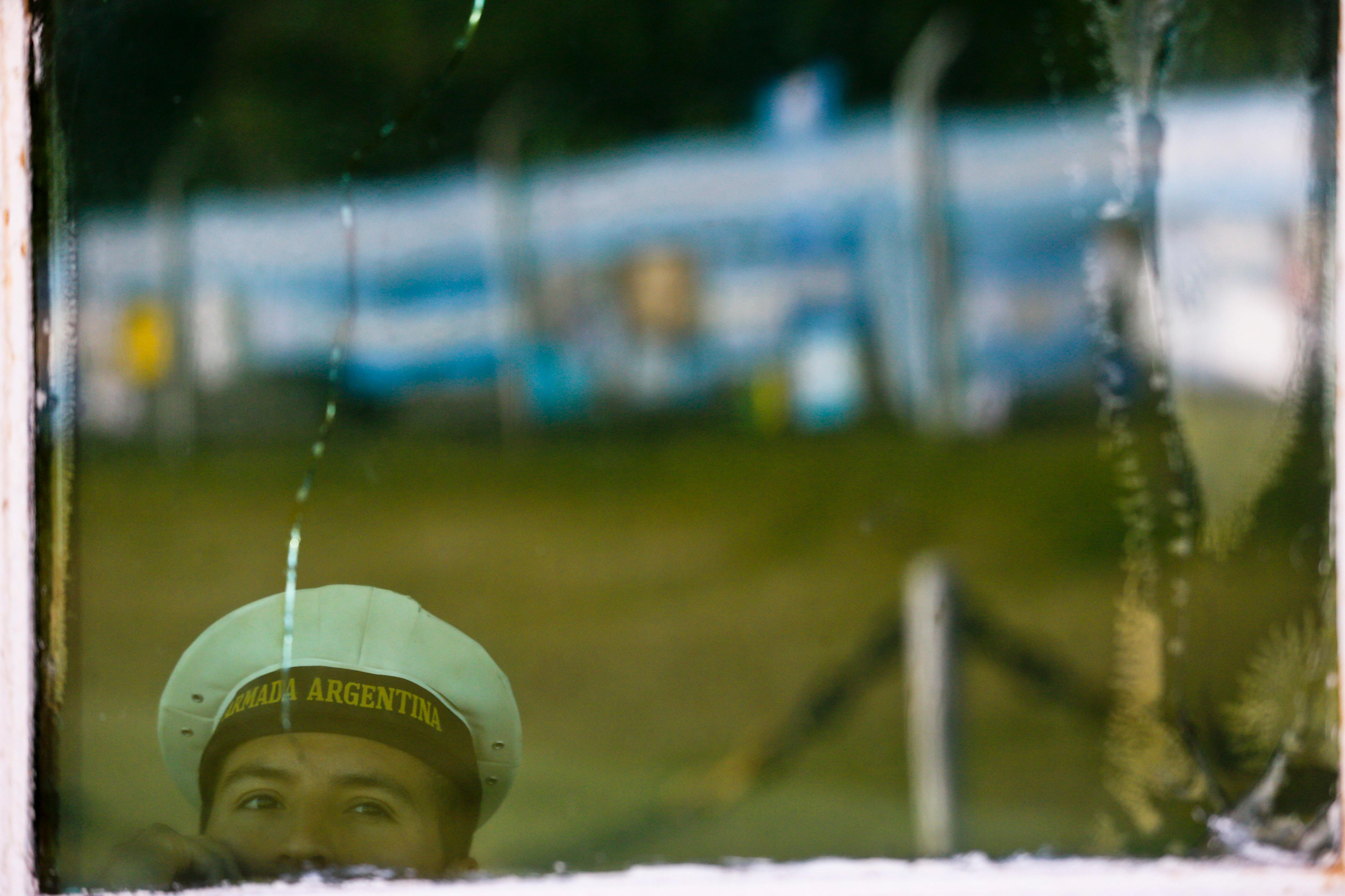 A seaman looks out from a checkpoint window that shows the reflection of a fence blanketed with national flags and homemade signs in support of submarine crew members of the missing  ARA San Juan, at the naval base in Mar de Plata, Argentina, Thursday, Nov. 23, 2017. More help was arriving in a multinational search Thursday for the Argentine submarine with 44 crew members as concern grew that the vessel's oxygen supply could soon start to run out. (AP Photo/Esteban Felix)