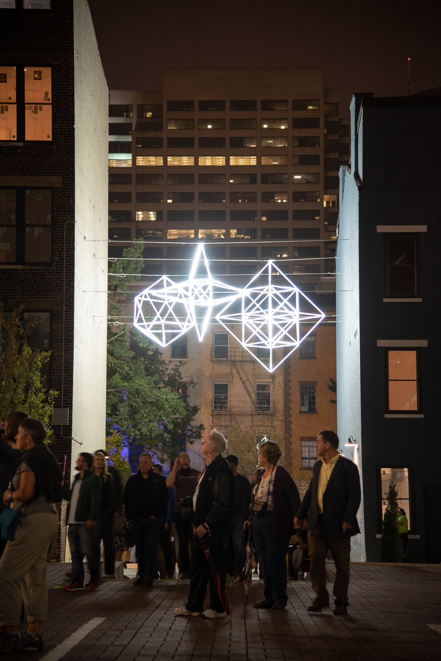 PICTURED NEIGHBORHOOD: Downtown / Illuminated hanging geometric shapes hang in a passageway between Court Street and Central Parkway. / Image: Phil Armstrong // Published: 10.12.19