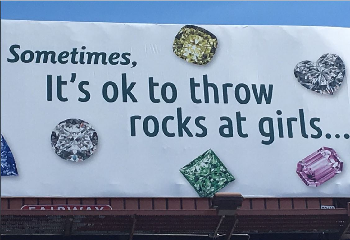 "About 15 demonstrators picketed with signs outside Spicer-Greene jewelers on Patton Avenue downtown. They're upset about a new billboard near the Jeff Bowen Bridge that says, ""Sometimes it's OK to throw rocks at girls,""and shows seven gemstones. (Photo credit: WLOS staff)"