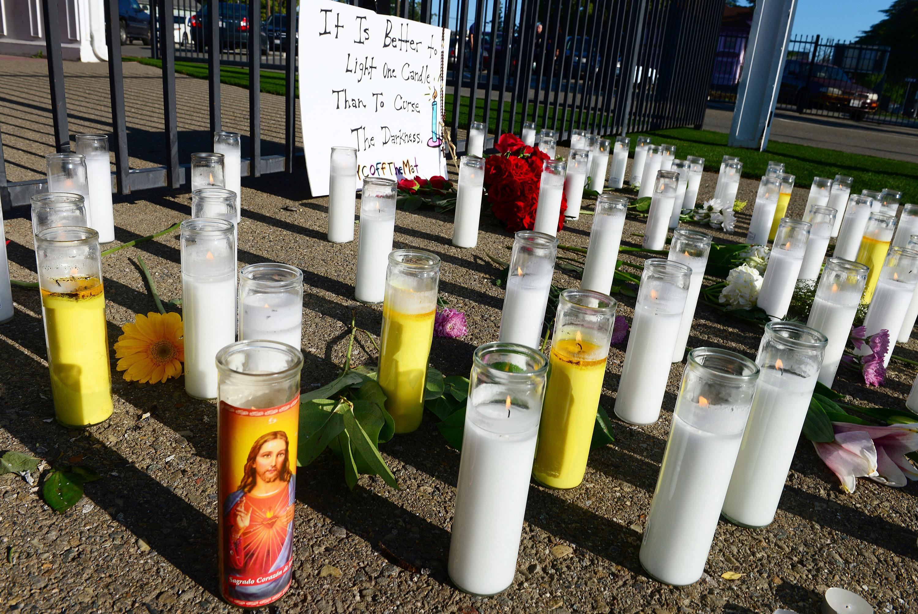 A memorial of candles and flowers grows at the scene of Tuesday's triple homicide shooting near Catholic Charities in downtown Fresno, Calif., on Wednesday, April 19, 2017. (Craig Kohlruss /The Fresno Bee via AP)