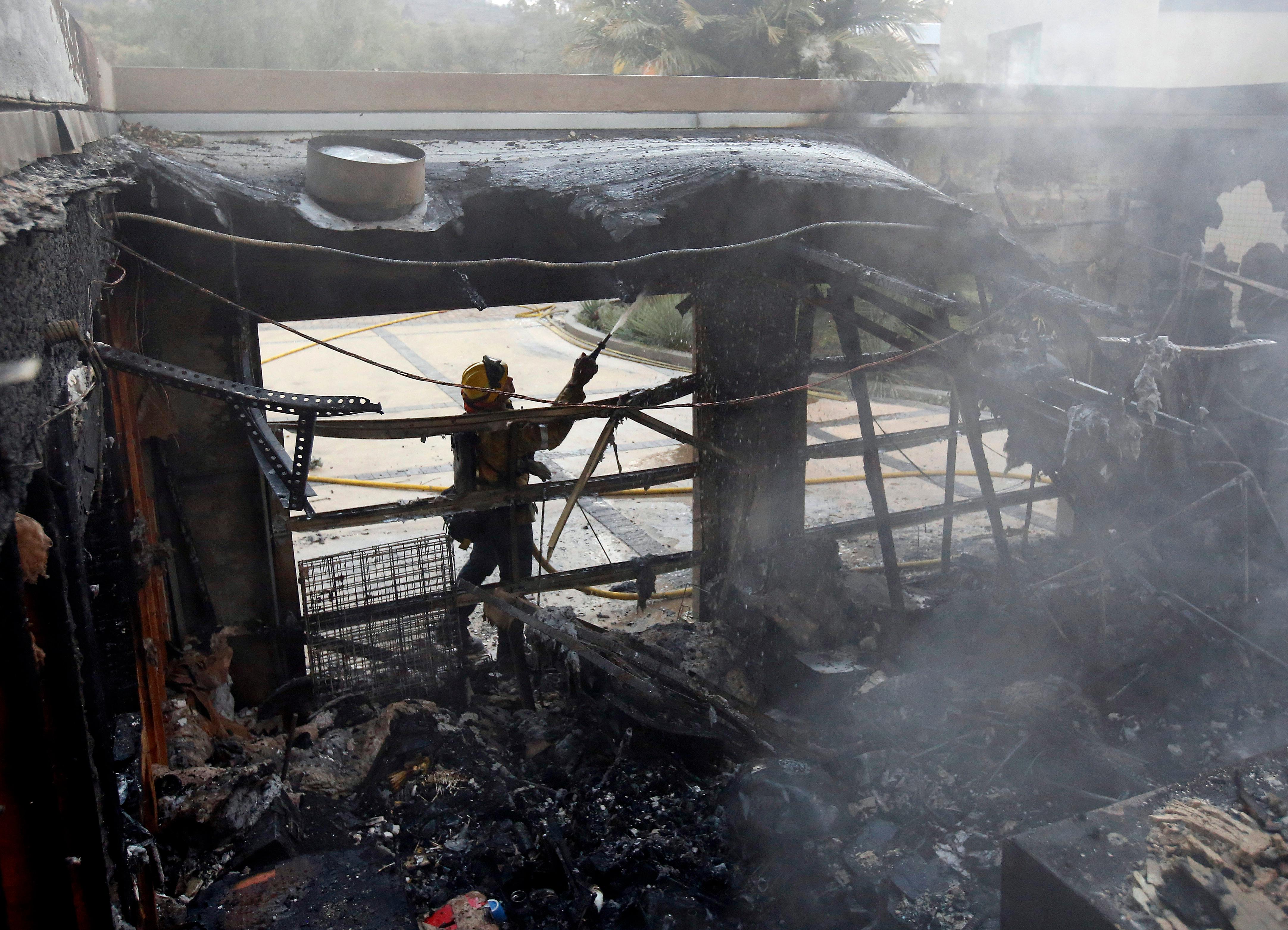 Firefighter Nick Gonzalez-Pomo, of the San Rafael Fire Department, waters down hot spots on a garage Tuesday, Oct. 10, 2017, in Napa, Calif. Wildfires whipped by powerful winds swept through the California wine country sending thousands fleeing as flames rages unchecked through high-end resorts, grocery stores and tree-lined neighborhoods.(AP Photo/Rich Pedroncelli)
