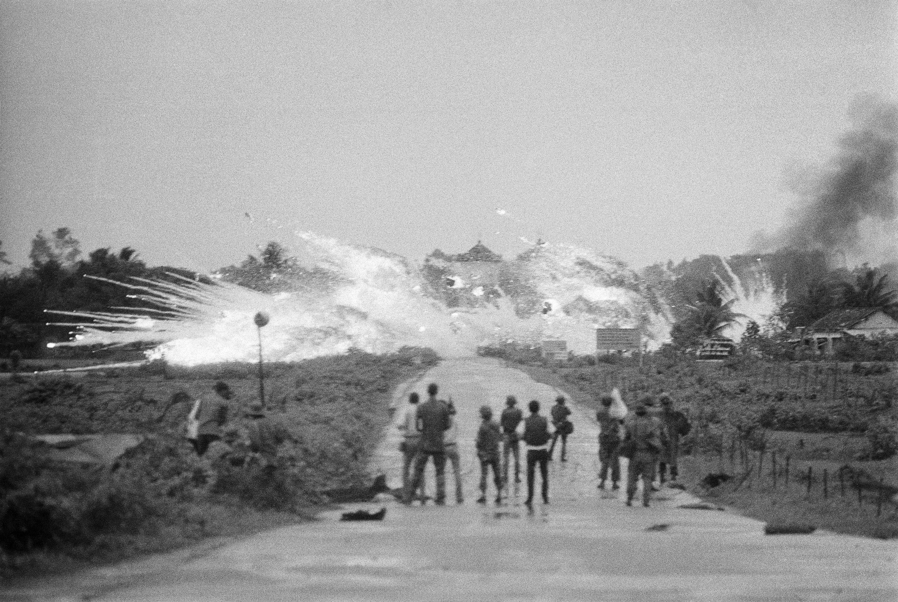 In this June 8, 1972 file photo, vombs with a mixture of napalm and white phosphorus jelly dropped by Vietnamese AF Skyraider bombers explode across Route-1, amidst homes and in front of the Cao Dai temple in the outskirts of Trang Bang, Vietnam. In the foreground are Vietnamese soldiers and journalists from various international news organizations. The towers of the Trang Bang Cao Dai temple are visible in the centre of the explosions. NICK UT/THE ASSOCIATED PRESS