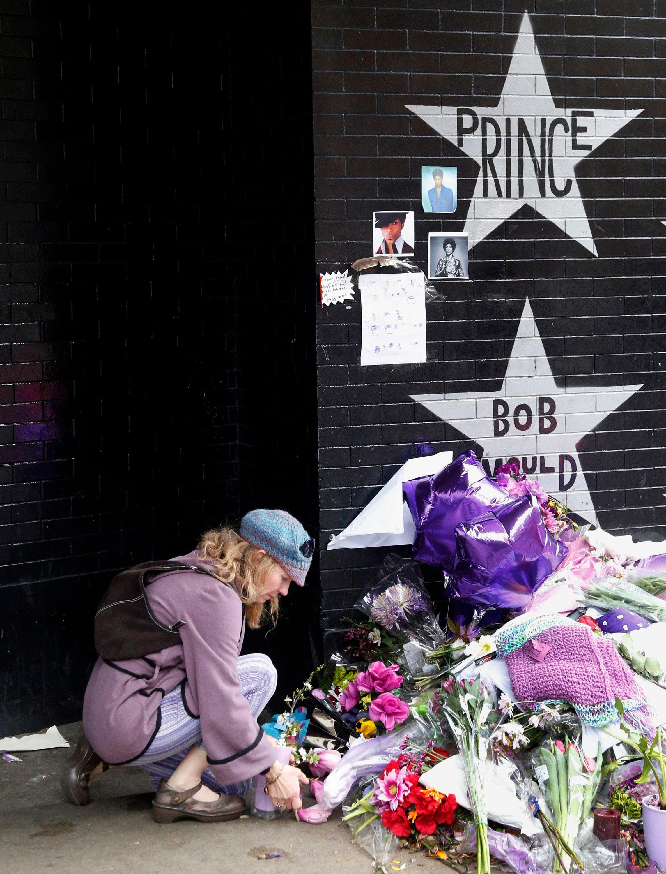 "FILE - In this April 22, 2016 file photo, a woman places flowers at a memorial at First Avenue in Minneapolis where pop super star Prince often performed. At his home and recording studio-turned-museum, a full four days of events are on tap for the one-year anniversary of his death on April 21, 2016, ranging from concert performances by the great one's former band mates to panel discussions on his legacy. Fans who can't afford those high-dollar tickets can head to a street party outside the club he made famous in ""Purple Rain."" (AP Photo/Jim Mone, File)"