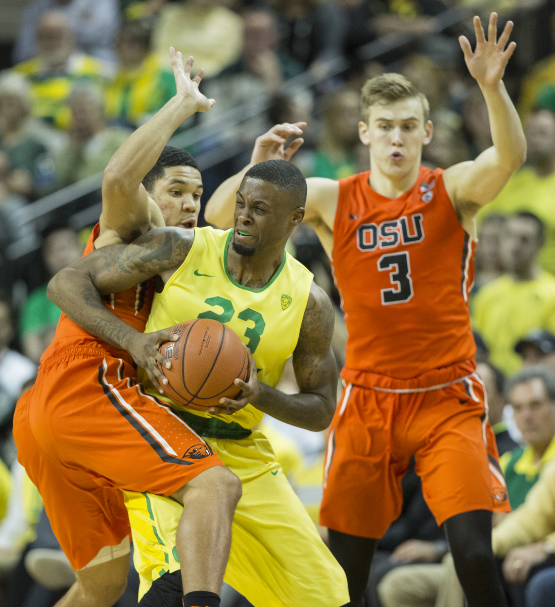 Oregon's Elgin Cook (23) looks to pass out of a half court trap by Oregon State's Tres Tinkle (3) and Malcolm Duvivier (11). After opening up a huge lead in the first half, the Ducks breezed to a 91-81 win over Oregon State on Saturday night in front of a sold out crowd at Matthew Knight Arena. With the victory, the Ducks advance to 21-6 on the year and 9-4 in conference play. Eric Cech, Oregon News Lab