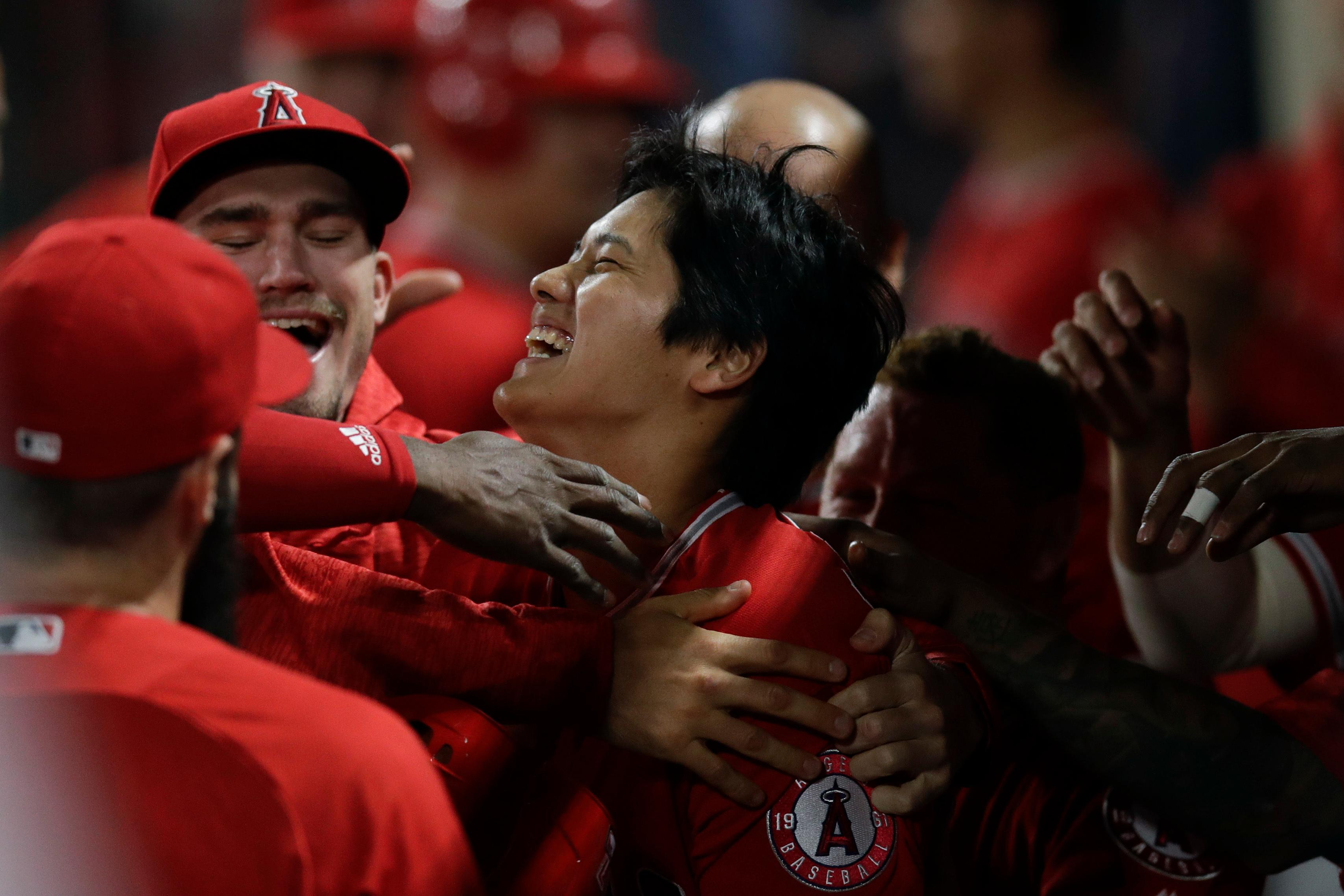 Los Angeles Angels starting pitcher Shohei Ohtani, center, of Japan, celebrates his three-run home run in the dugout during the first inning of a baseball game against the Cleveland Indians, Tuesday, April 3, 2018, in Anaheim, Calif. (AP Photo/Jae C. Hong)