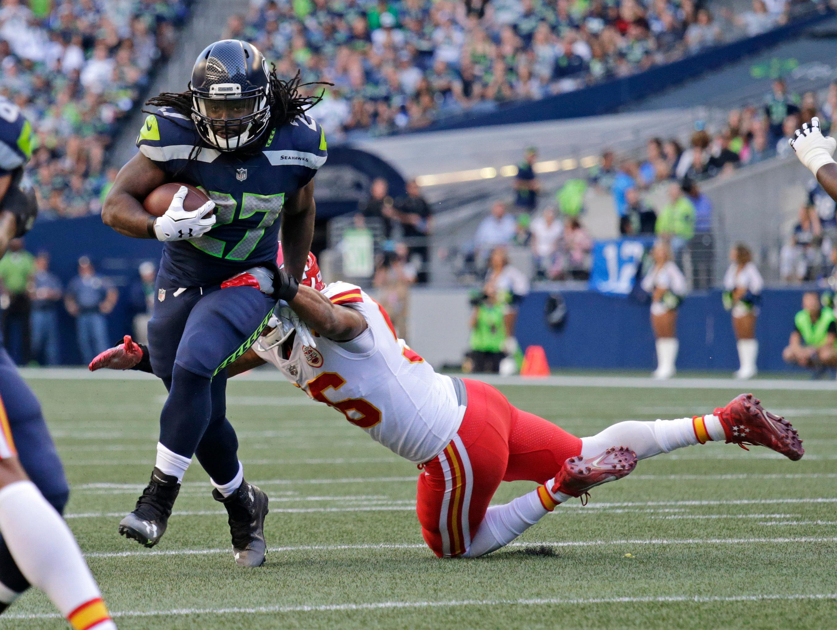 Seattle Seahawks running back Eddie Lacy, left, breaks a tackle by Kansas City Chiefs inside linebacker Derrick Johnson, right, during the first half of an NFL football preseason game, Friday, Aug. 25, 2017, in Seattle. (AP Photo/John Froschauer)