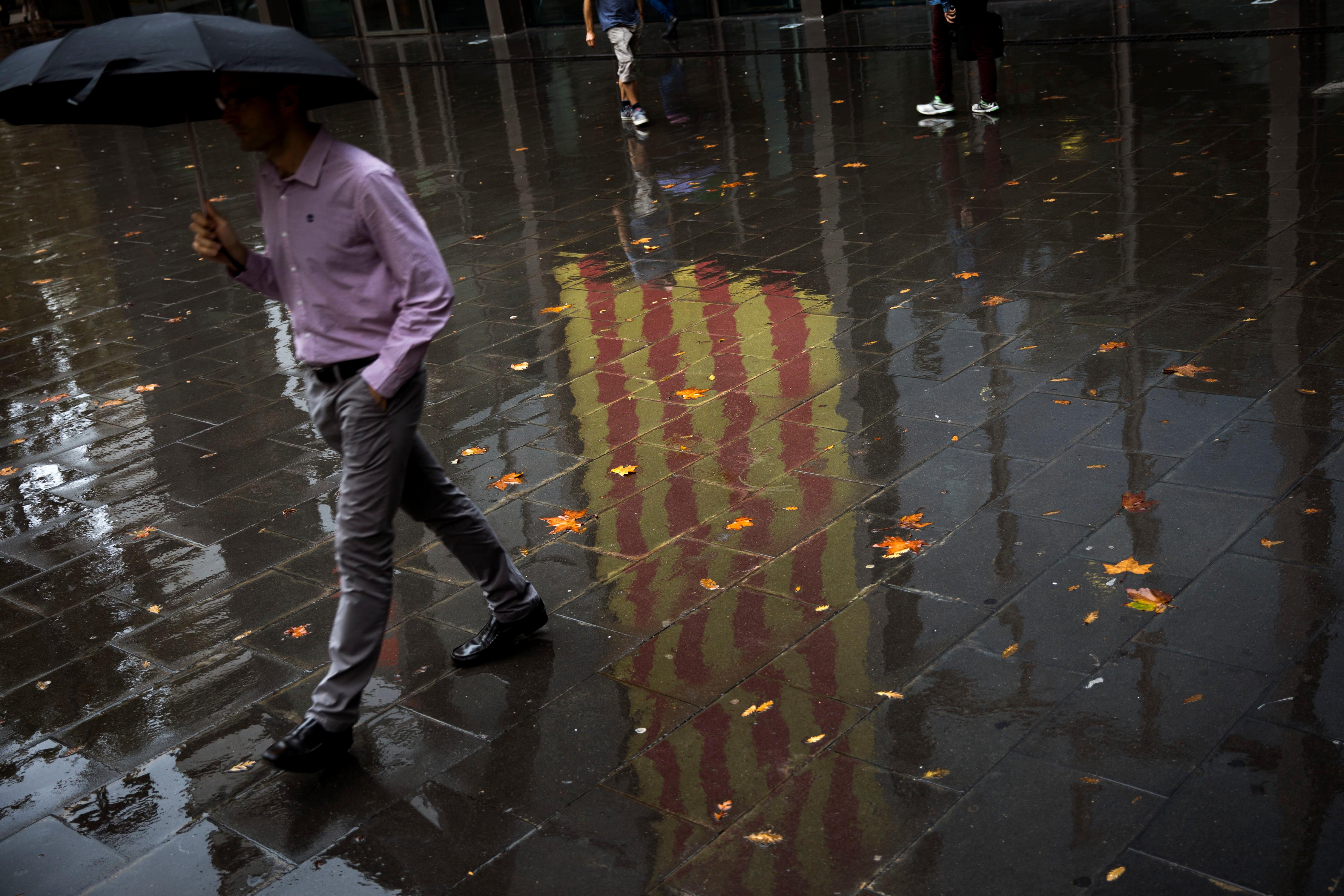 People walk past a Catalan flag reflected on the wet ground in Barcelona, Spain, Thursday, Oct. 19, 2017. Spain's government on Thursday immediately rejected a threat by Catalonia's leader to declare independence unless talks are held, calling a special Cabinet session for the weekend to activate measures to take control of the region's semi-autonomous powers. (AP Photo/Emilio Morenatti)