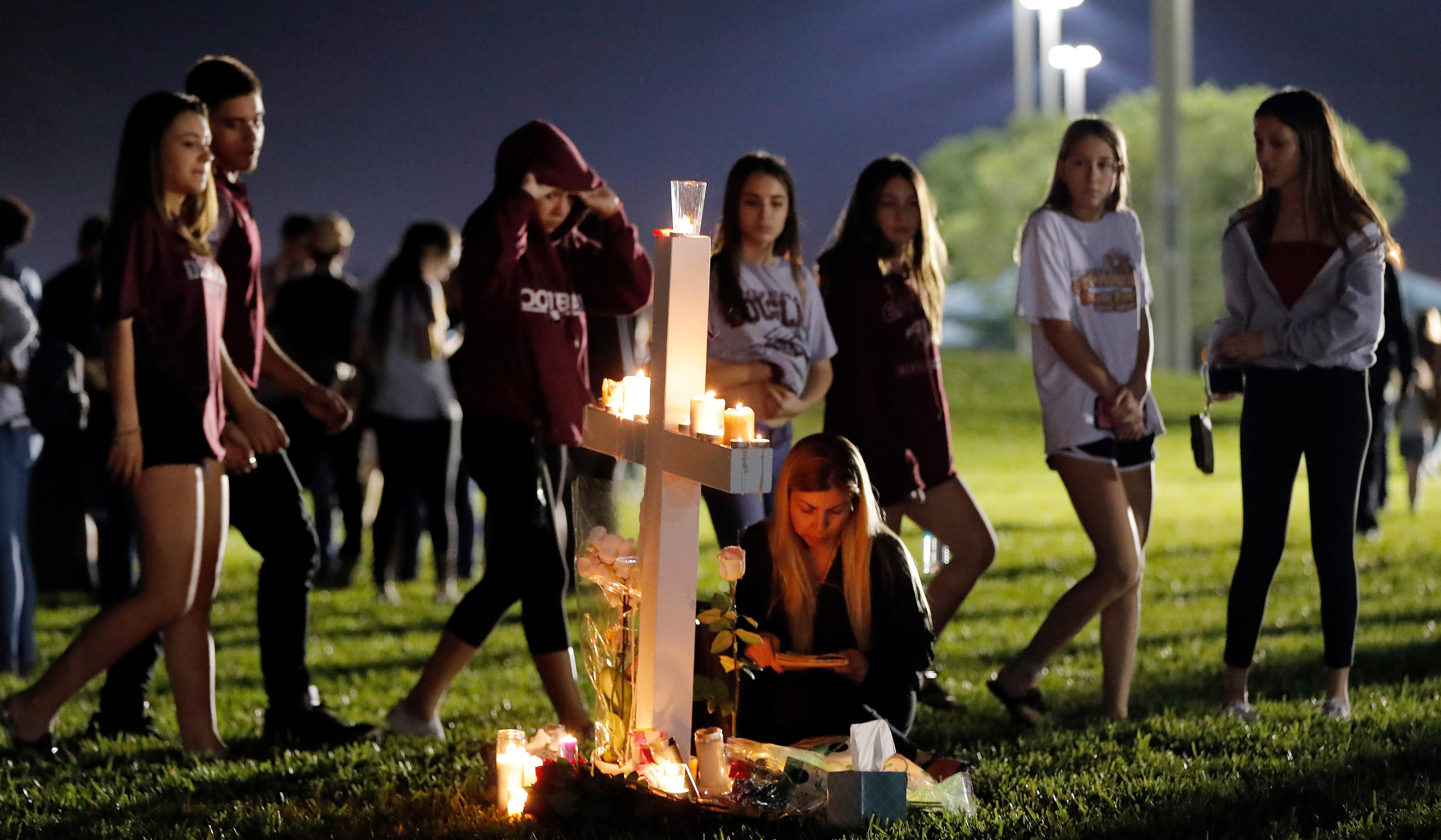 Students walk past one of seventeen crosses after a candlelight vigil for the victims of the Wednesday shooting at Marjory Stoneman Douglas High School, in Parkland, Fla., Thursday, Feb. 15, 2018. Nikolas Cruz, a former student, was charged with 17 counts of premeditated murder on Thursday. (AP Photo/Gerald Herbert)