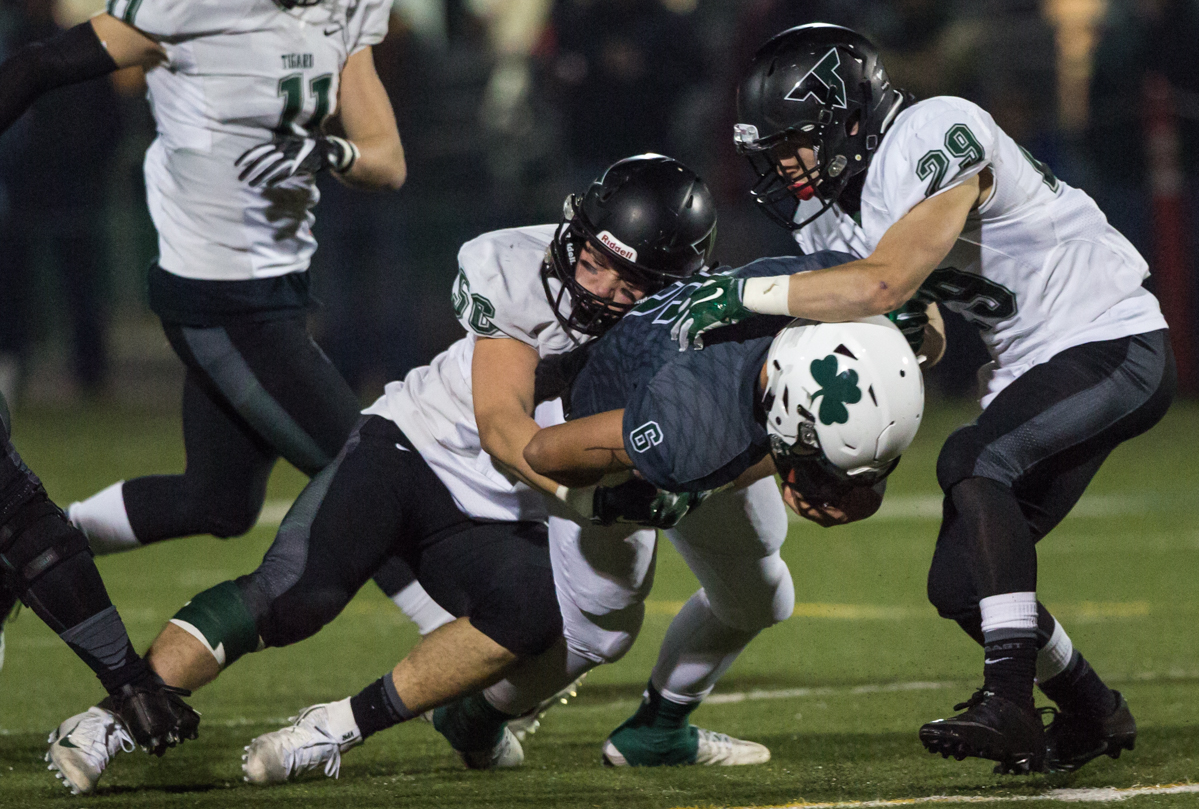 Sheldon Irish quarterback Zach Diehl (#6) is tackled by Tigard defenders Justin Lyons (#56) and Spencer Smith (#29).  The Tigard Tigers defeated Sheldon 27-0 to advance to the OSAA 6A semifinals.  Photo by Austin Hicks, Oregon News Lab