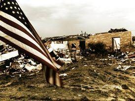 An American flag flies in front of the ruins of the school.