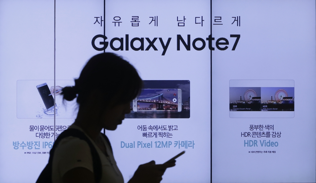FILE - In this Friday, Sept. 2, 2016, file photo, a woman walks by an advertisement of the Samsung Electronics Galaxy Note 7 smartphone at the company's showroom in Seoul, South Korea. The Federal Aviation Administration said Thursday night, Sept. 8, 2016, that because of recent fire reports involving the Galaxy Note 7 smartphone, passengers shouldn't use or charge one or stow one in checked baggage. The three biggest U.S. airlines: American, Delta and United, said Friday that they were studying the FAA warning but it was unclear how they would make sure that passengers keep the Samsung devices powered off. (AP Photo/Ahn Young-joon, File)