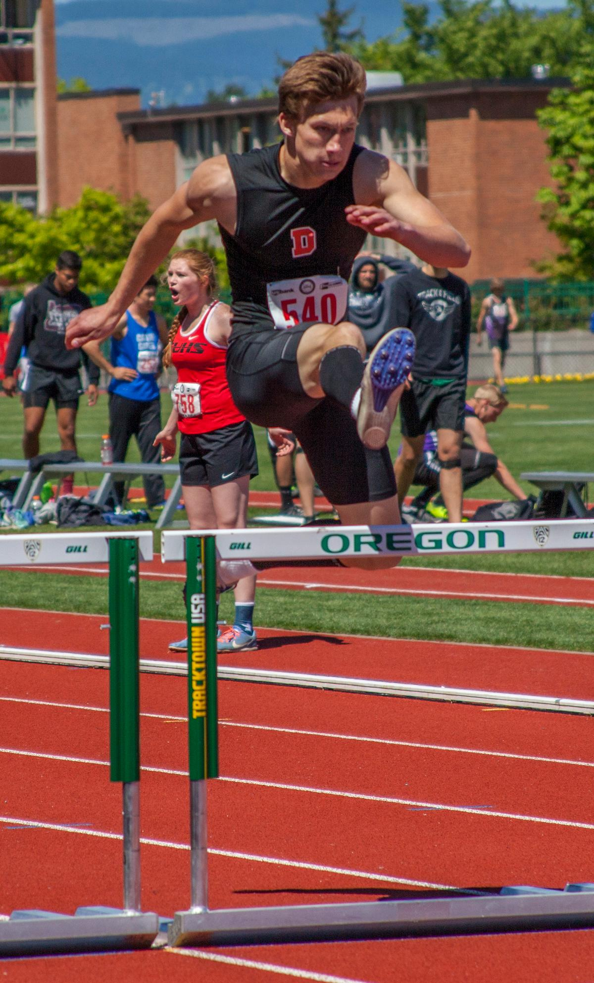 Jacob Deming from Dallas High School wins the Boys 300 Meter Hurdles 5A Prelims event with the time of 39.62 at the OSAA Track and Field State Championships at Hayward Field. Photo by Vannie Cooper, Oregon News Lab