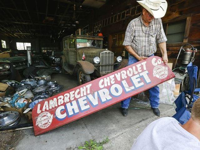 Art Nordstrom holds a sign at the former Lambrecht Chevrolet car dealership in Pierce.