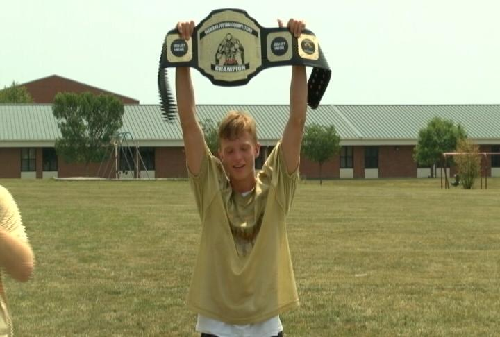 Freshman Tommy Job hoists Highland's Championship Belt following the Cougars weekly conditioning competition.