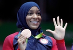 Ibtihaj Muhammad of the United States pose with her bronze medals on the podium after the women's team sabre fencing event at the 2016 Summer Olympics in Rio de Janeiro, Brazil, Saturday, Aug. 13, 2016. (AP Photo/Vincent Thian)