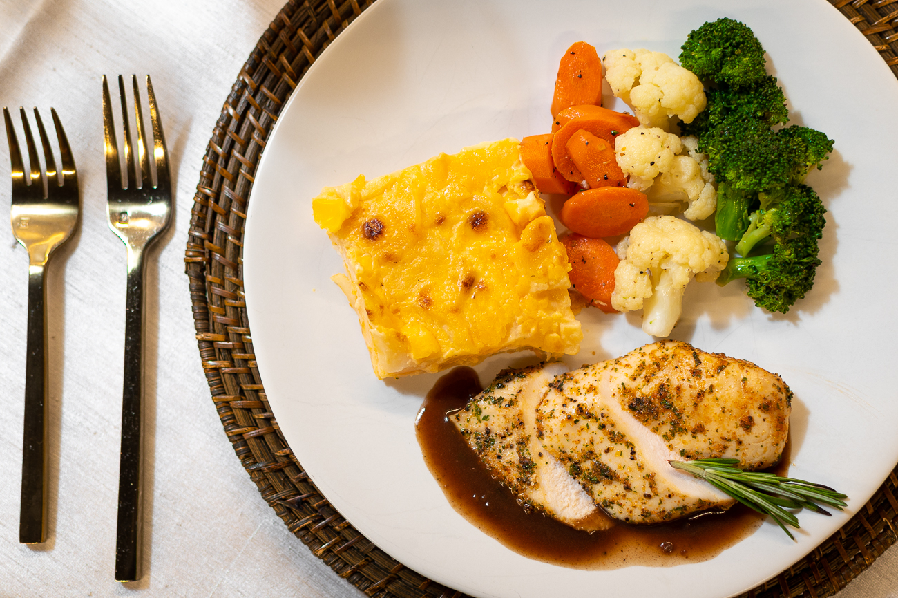The Holiday Dinner Buffet. Pictured: roasted chicken breast with bourbon rosemary sauce, au gratin potatoes, broccoli, cauliflower, and carrots. / Image: Phil Armstrong, Cincinnati Refined // Published: 11.6.20