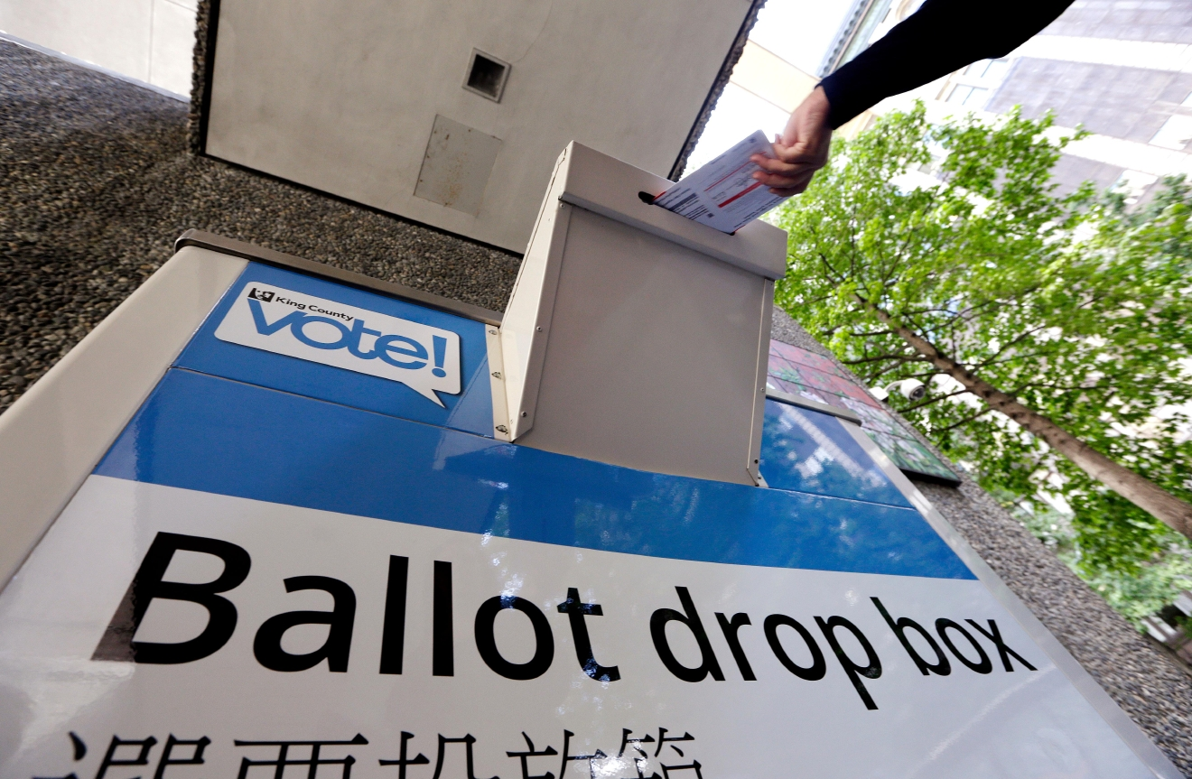 A voter drops a ballot into a ballot drop box Tuesday, Aug. 2, 2016, in Seattle. Washington's voters are weighing in on dozens of races across the state as they winnow their choices for offices ranging from Congress to the Legislature in the state's primary election. (AP Photo/Elaine Thompson)