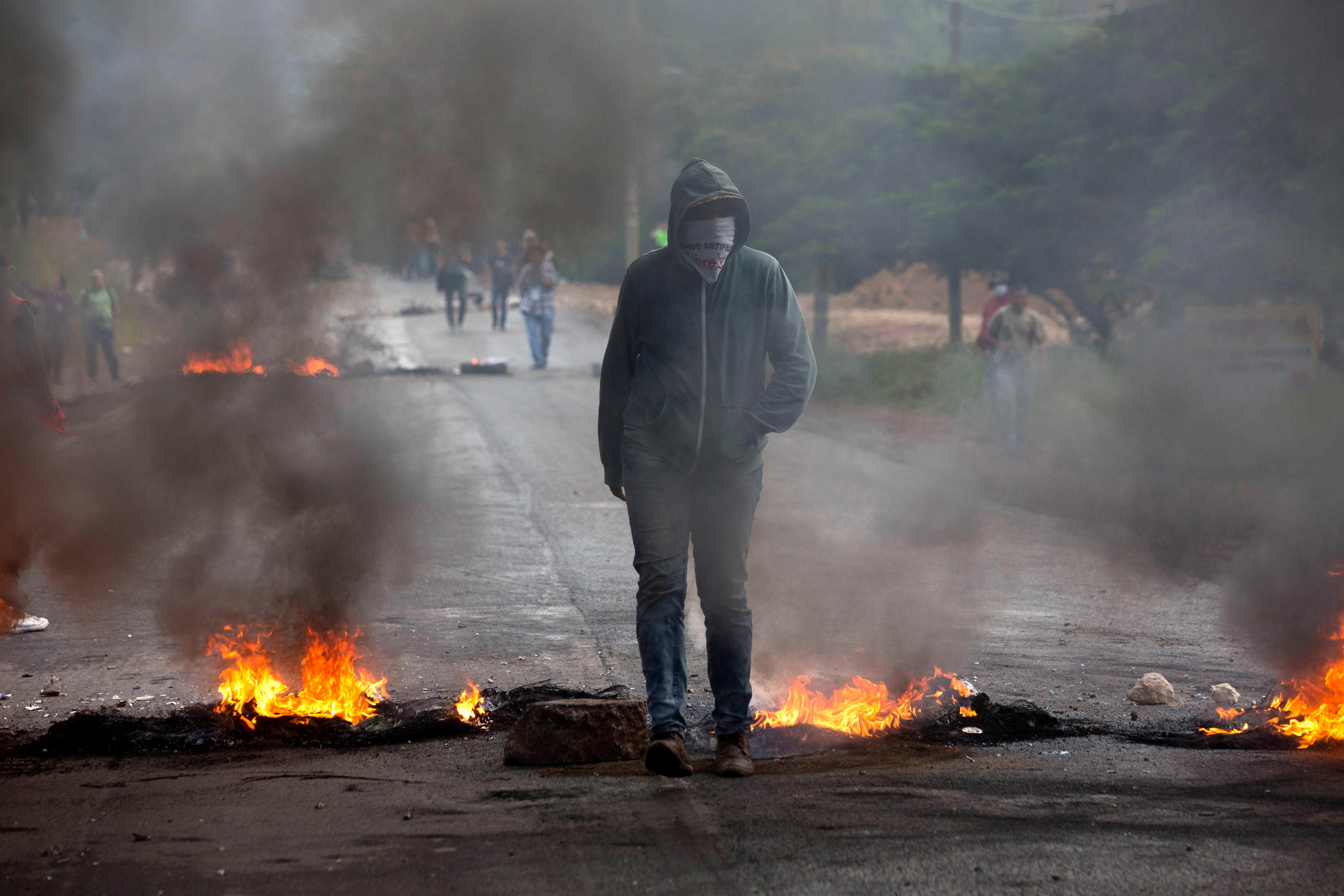 An anti-government protestor stands at a burning barricade erected by protesters to block the road to Valle de los Angeles, on the outskirts of Tegucigalpa, Honduras, Thursday, Dec. 7, 2017. Eight Latin American governments on Wednesday applauded Honduras' willingness to recount disputed votes in the presidential elections, but questions remain about how thorough that recount will be. (AP Photo/Moises Castillo)