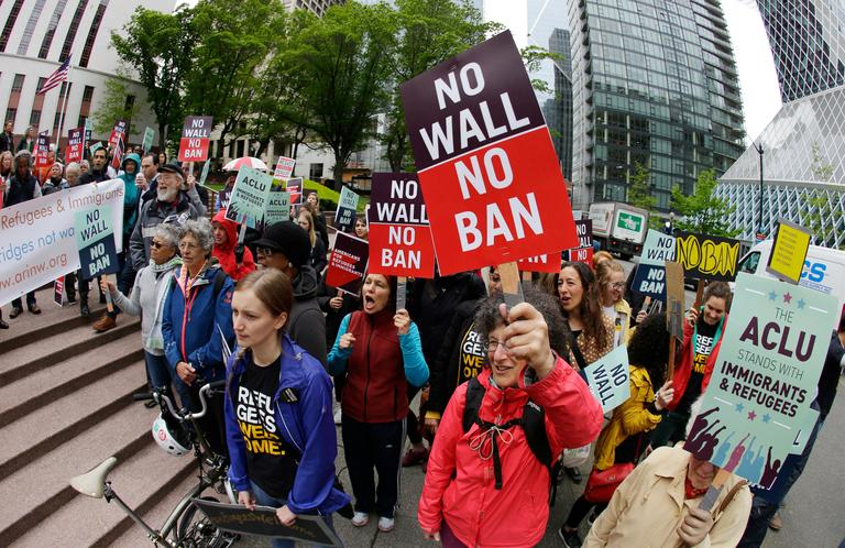 FILE - In this May 15, 2017, file photo, protesters wave signs and chant during a demonstration against President Donald Trump's revised travel ban outside a federal courthouse in Seattle. The U.S. Supreme Court's decision allowing Trump's third travel ban to take effect, at least for now, has intensified the attention on a legal showdown before three judges in Seattle who have previously been cool to the administration's efforts. Ninth U.S. Circuit Court of Appeals Judges Ronald Gould, Richard Paez and Michael Hawkins are scheduled to hear arguments Wednesday afternoon, Dec. 6, 2017 in Hawaii's challenge to the latest version of the travel ban.  (AP Photo/Ted S. Warren, File)
